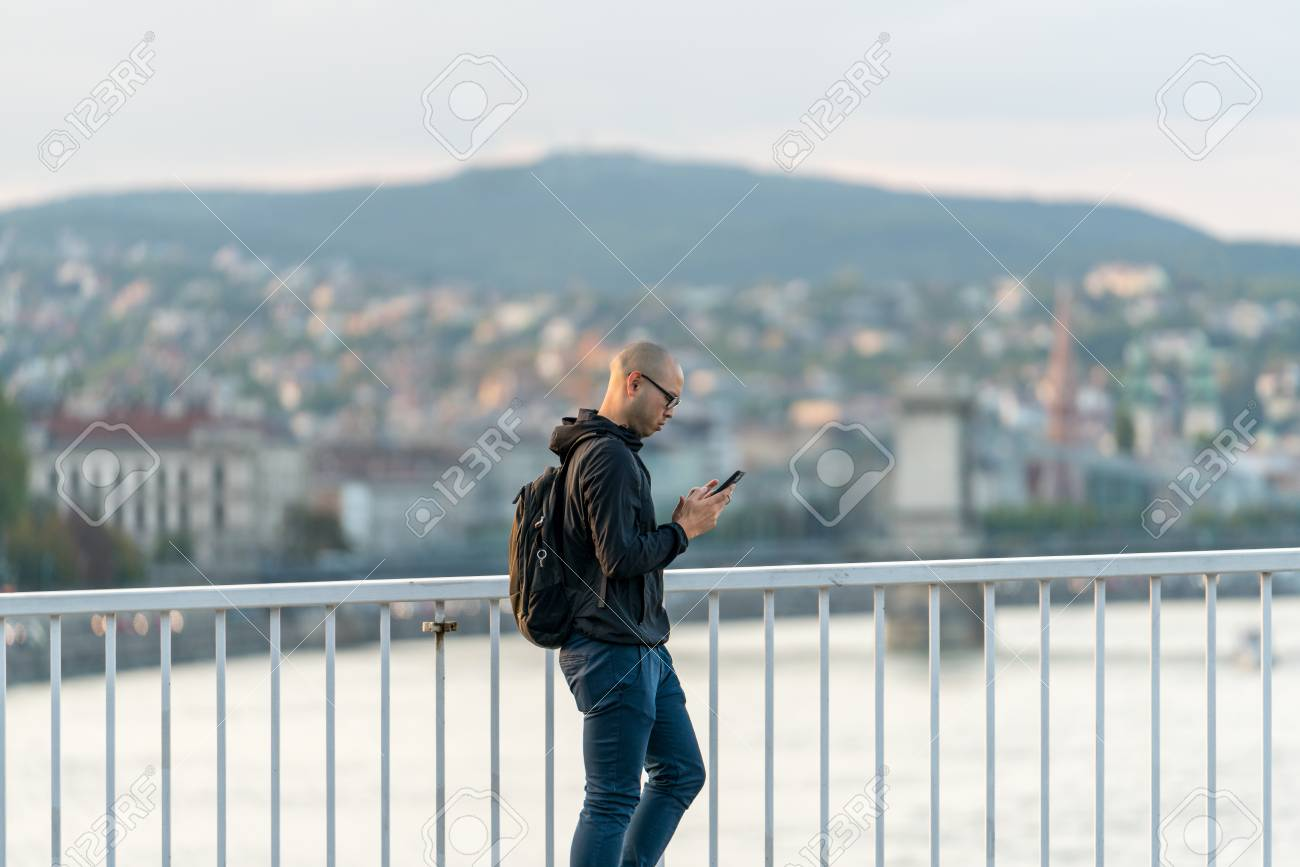 Budapest, Hungary - September 25, 2017: Close up side view of a pedestrian with glasses and backpack walking by a steel railing on a bridge with the city of Budapest Hungary in the background. Concentrated because he walk and looks at his mobile phone at  Stock Photo - 87197852