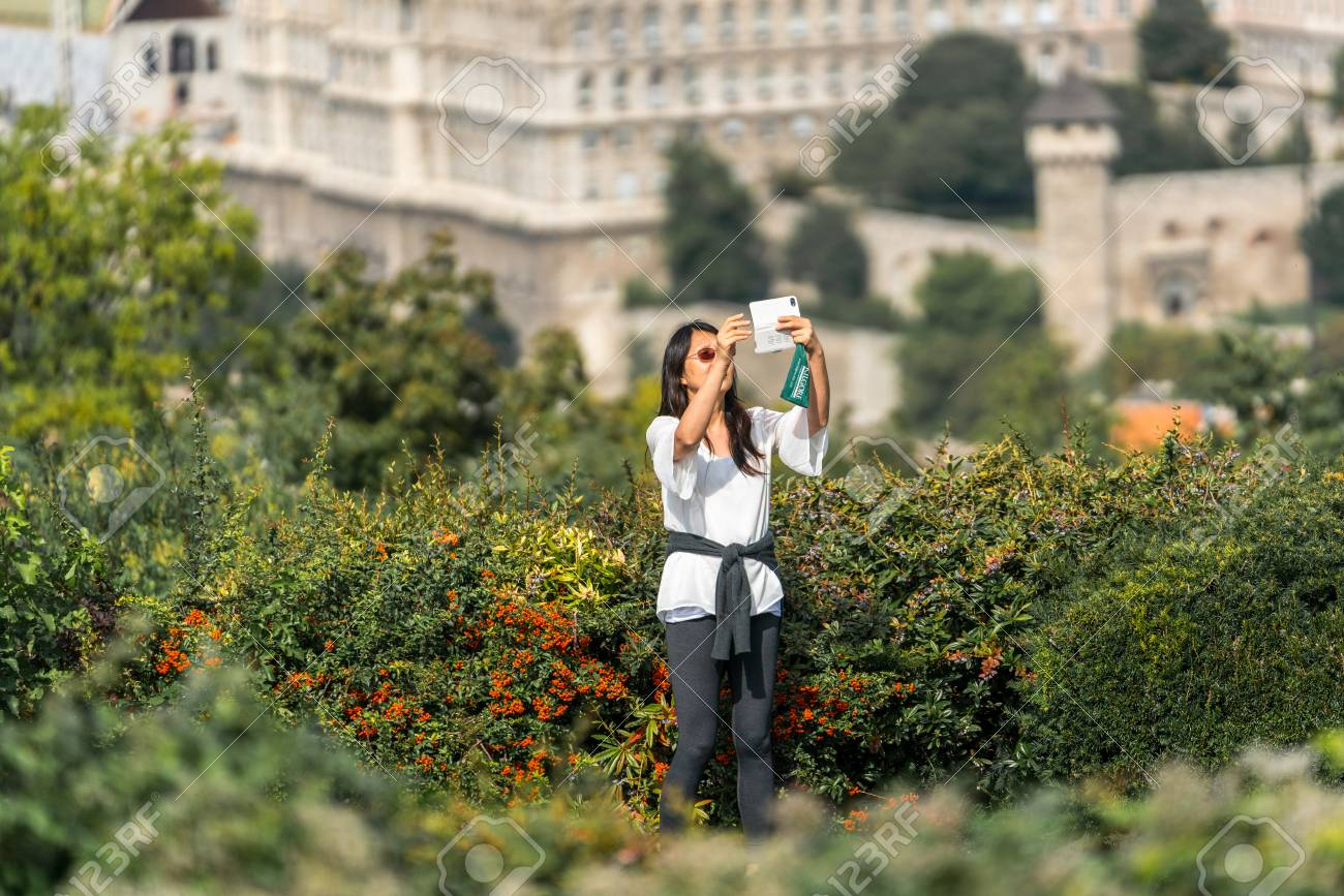 Budapest, Hungary - September 26, 2017: Selective focus front view of an asian female tourist standing in green bushes at a viewpoint up high to take a panoramic selfie picture with her mobile phone of the city Budapest Hungary below. Stock Photo - 87197854