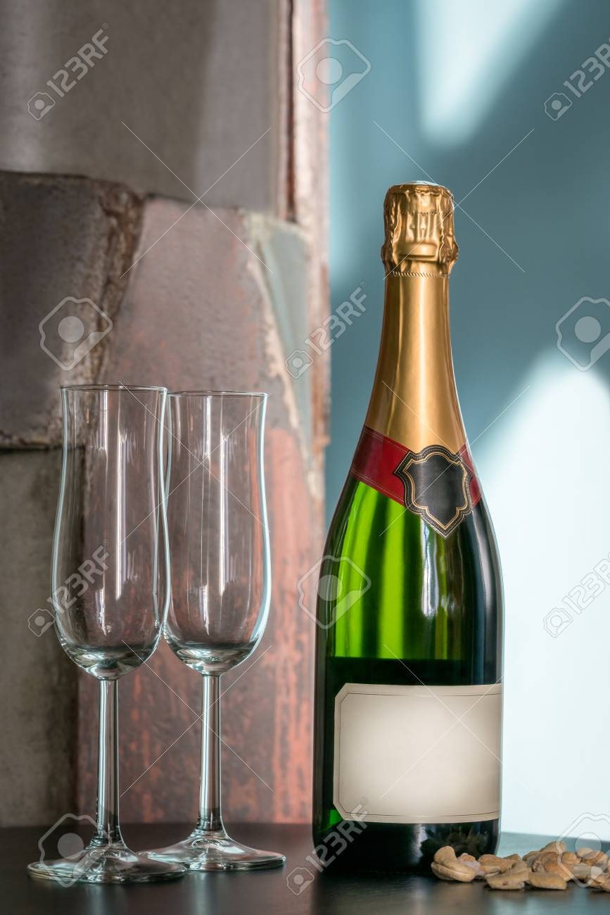 Still life shot of a unopened champagne bottle and two empty glasses on a table with snacks. Label with copy space. Stock Photo - 88491525