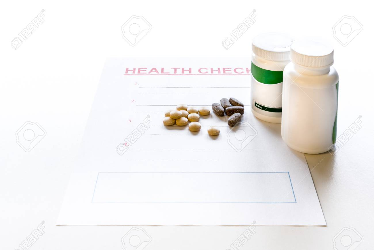 A blank health check form with medicine, vitamins and pills. Plastic medicine containers with label and copy space. Stock Photo - 90867727