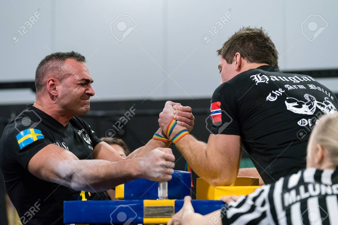 STOCKHOLM, SWEDEN - JANUARY 13, 2018: Profile view of a Swedish and Norwegian male arm wrestler and a referee in a match at the event Arm Battle of Sweden outside of Stockholm January 13, 2018. Stock Photo - 94169874