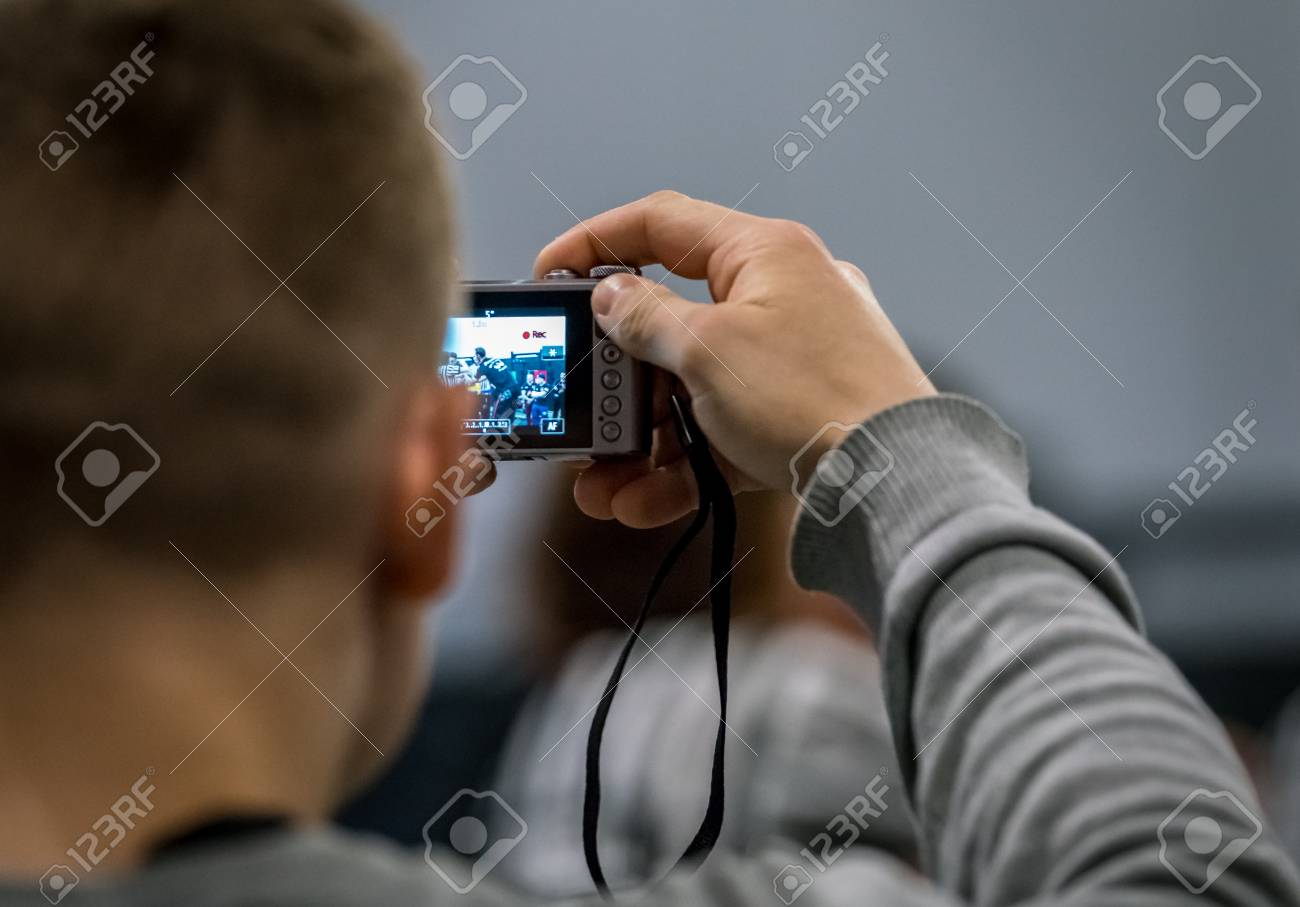 STOCKHOLM, SWEDEN - JANUARY 13, 2018: Back view close up of a man taking photo with a compact camera of sports outside of Stockholm January 13, 2018. Stock Photo - 94169883