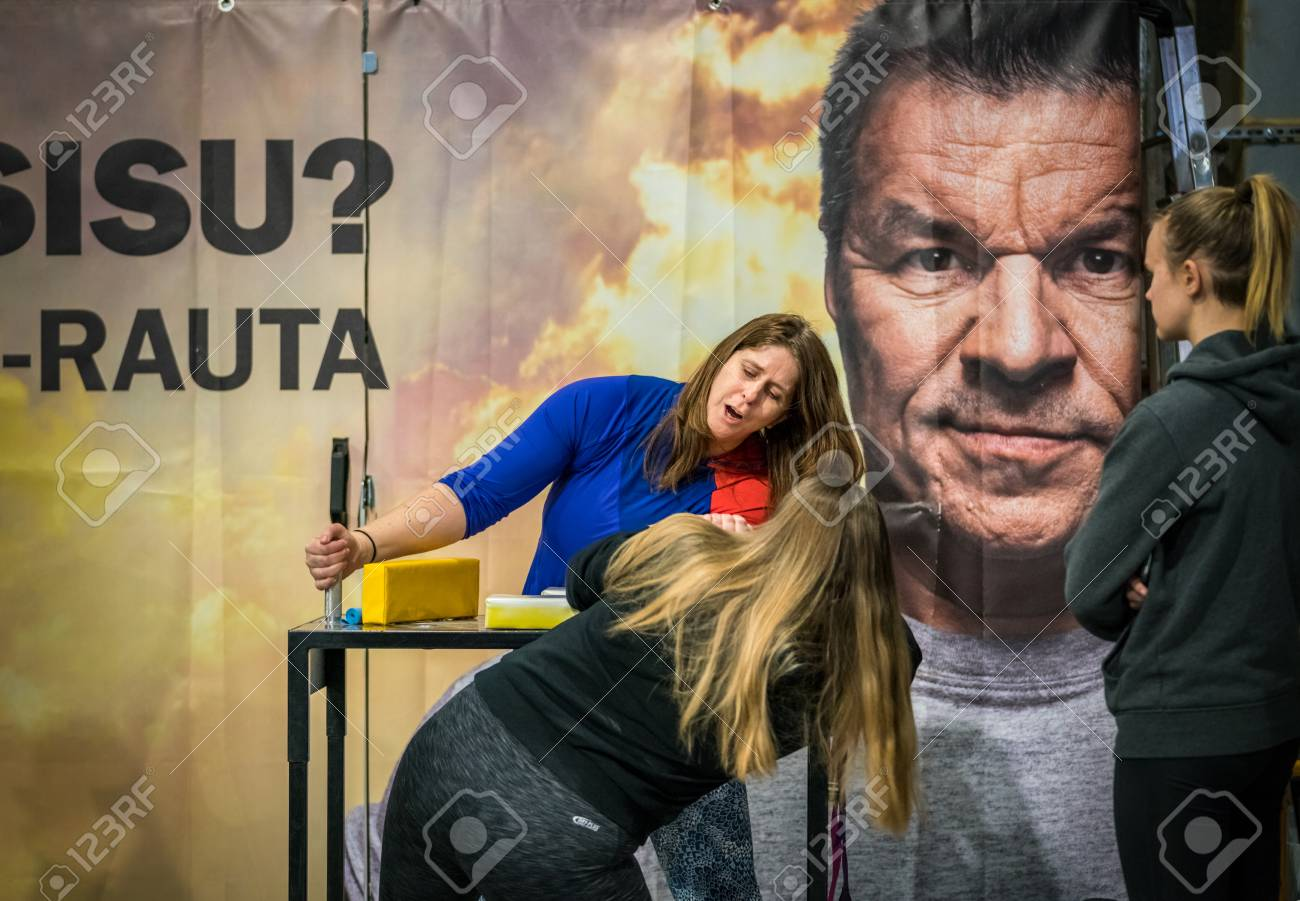 STOCKHOLM, SWEDEN - JANUARY 13, 2018: Two female arm wrestlers and one spectator training in front of a large ad during the event Arm Battle of Sweden outside of Sockholm January 13, 2018. Stock Photo - 94169887