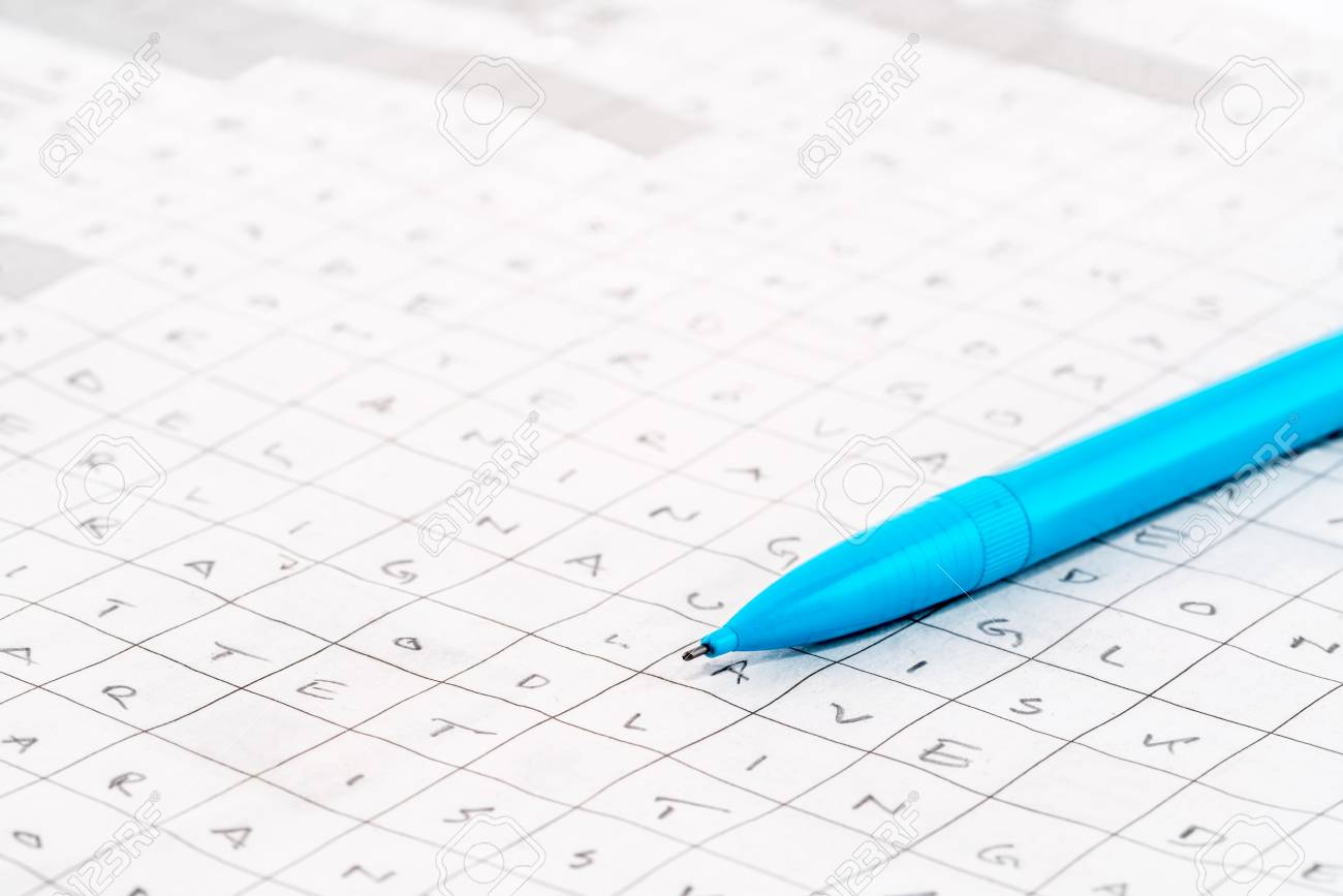 Leisure activity. Close-up of a blue pen on a newspaper crossword puzzle with letters. Stock Photo - 94689196