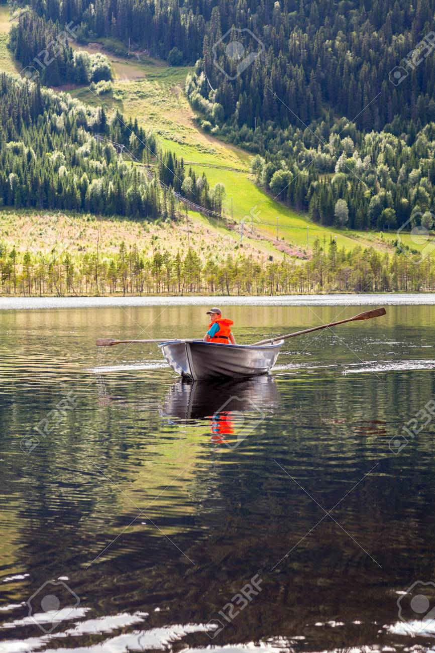 Boy in a rowing boat on a mountain lake with green hills and forest in the background. Stock Photo - 94664613