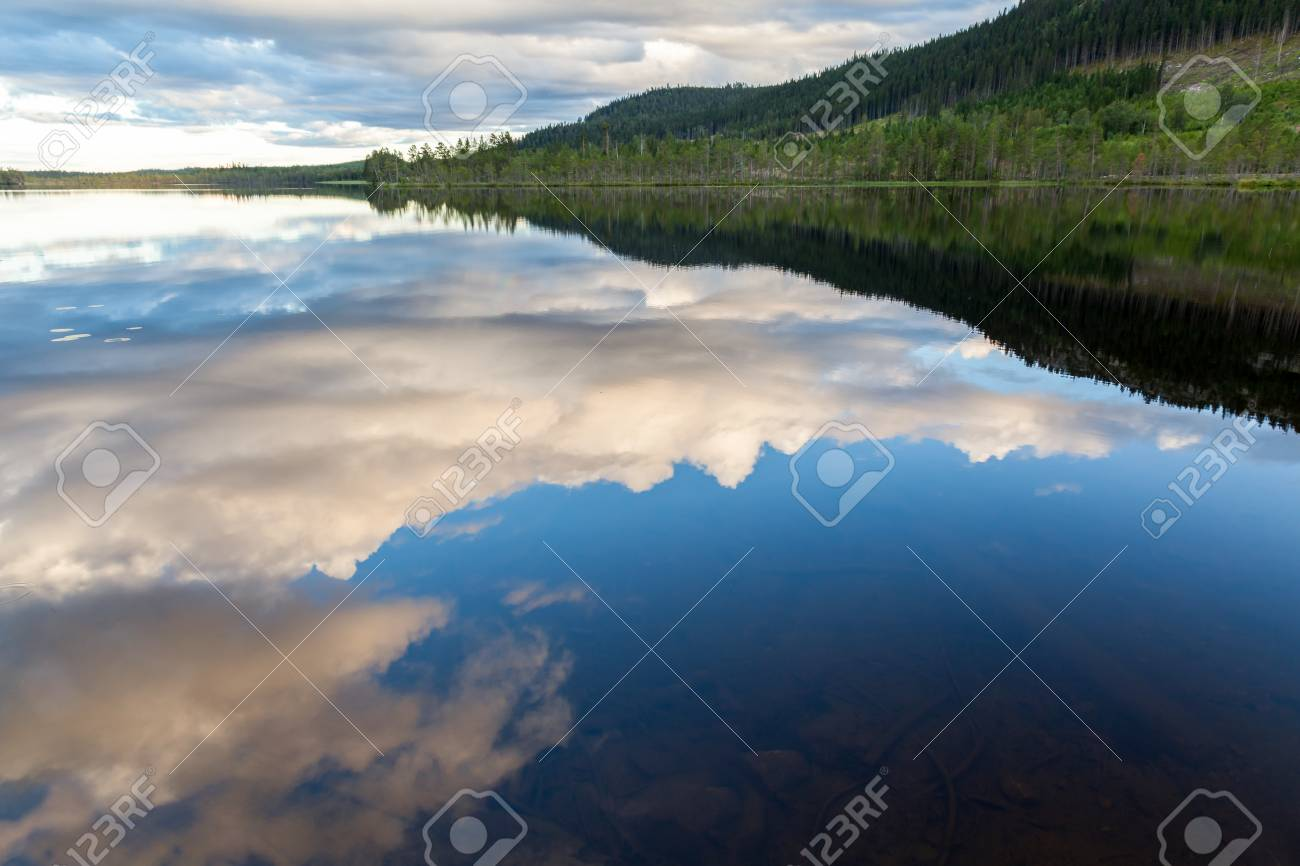 Beautiful landscape view of mountains, forest and cloudy sky reflection in calm water. Stock Photo - 94804768