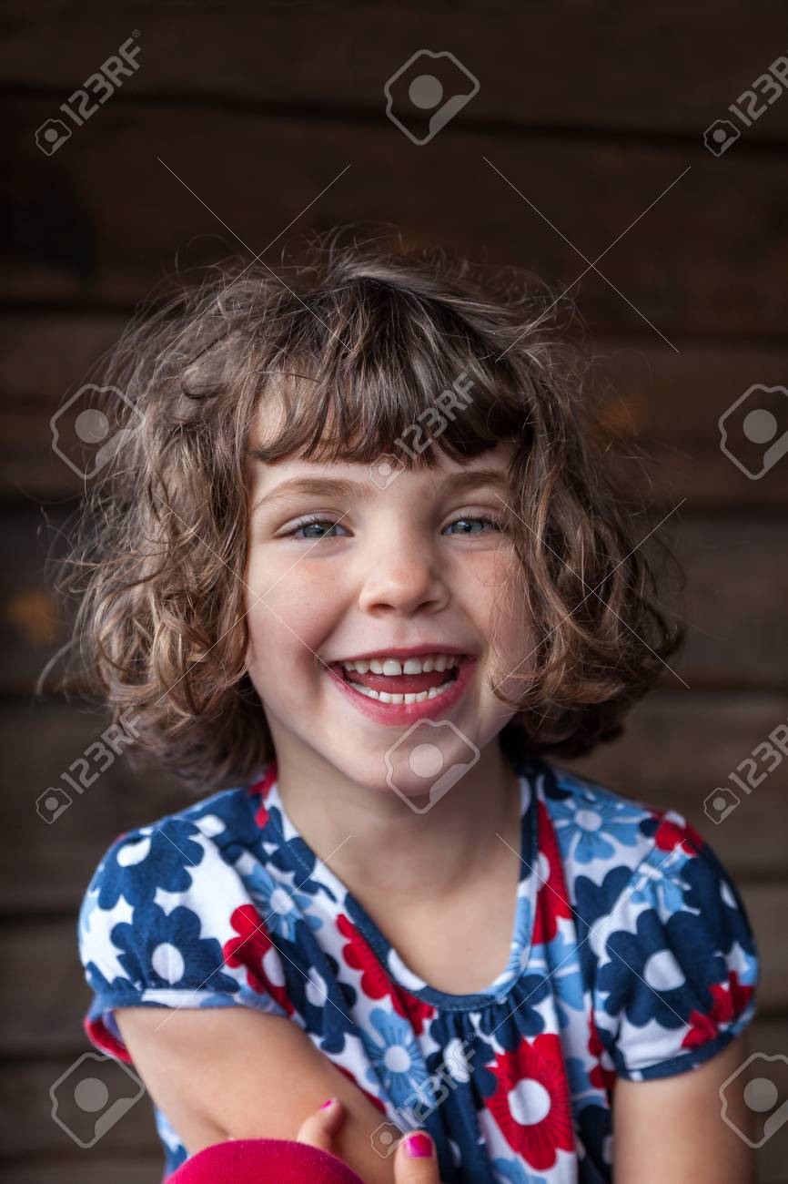 Close up summer portrait of a cute pretty smiling preschool girl with tangled hair and colorful dress. Stock Photo - 94938380