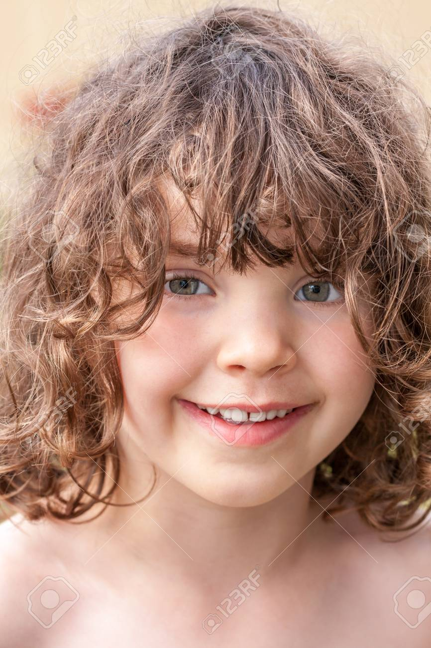 Close up summer portrait of a cute pretty smiling preeschool girl with tangled hair. Stock Photo - 94678288