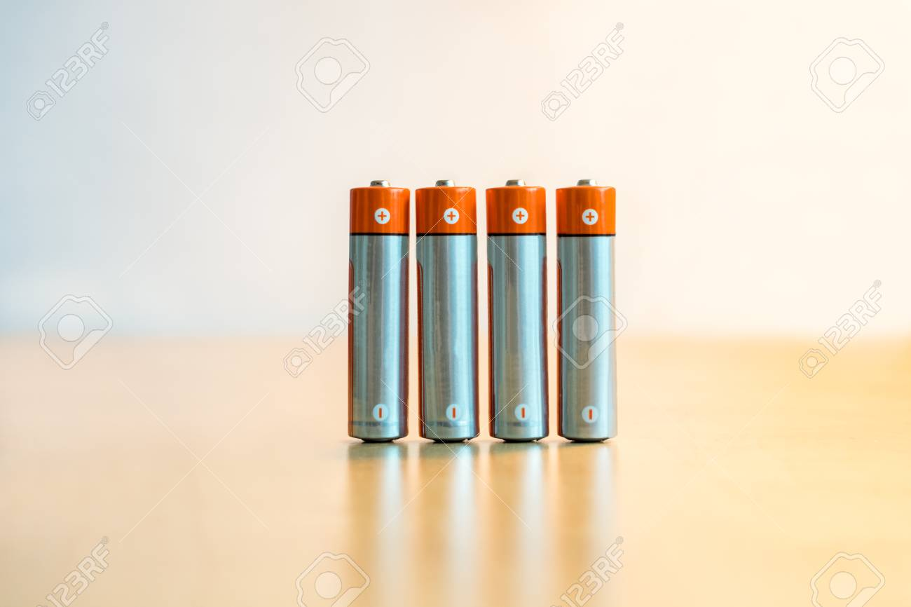 Close-up of four AA batteries standing on a table with plus and minus signs. Stock Photo - 94689197