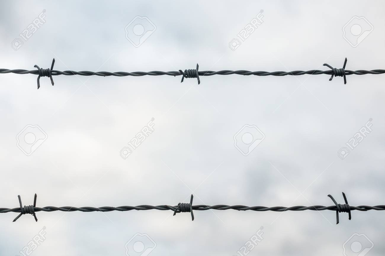 Close-up of barbed wire in two lines against cloudy sky. Stock Photo - 94938378