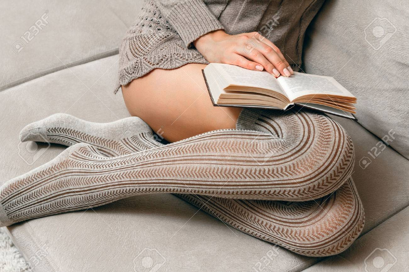 Excellent Young Beautiful Woman In A Knitted Sweater And Stockings Reading Cjindustries Chair Design For Home Cjindustriesco