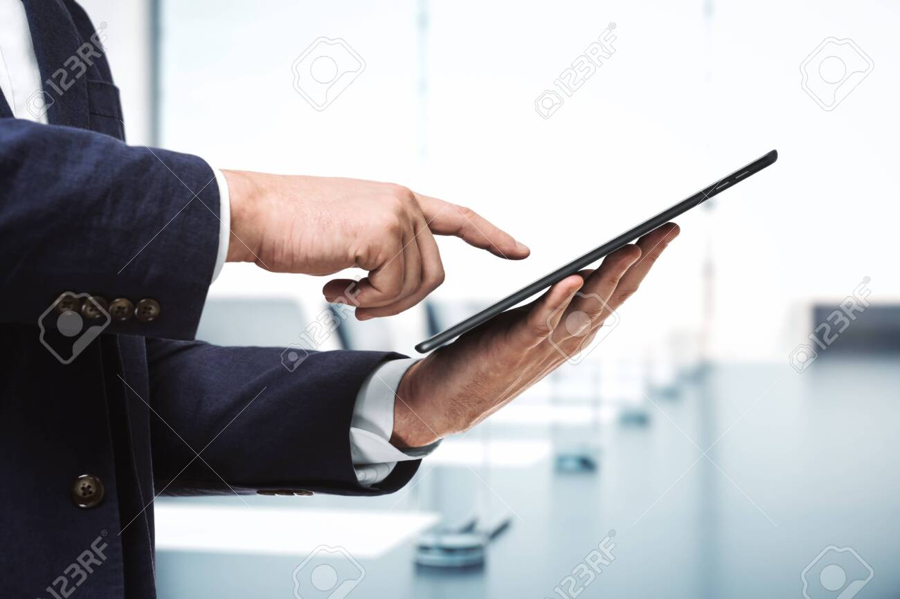 Man presses on the screen of a digital tablet in sunny boardroom, close up. Online technology concept - 143650597