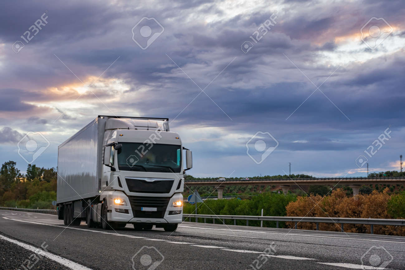 Refrigerated semi-trailer truck driving on a highway under a dramatic sunset sky. - 157817546