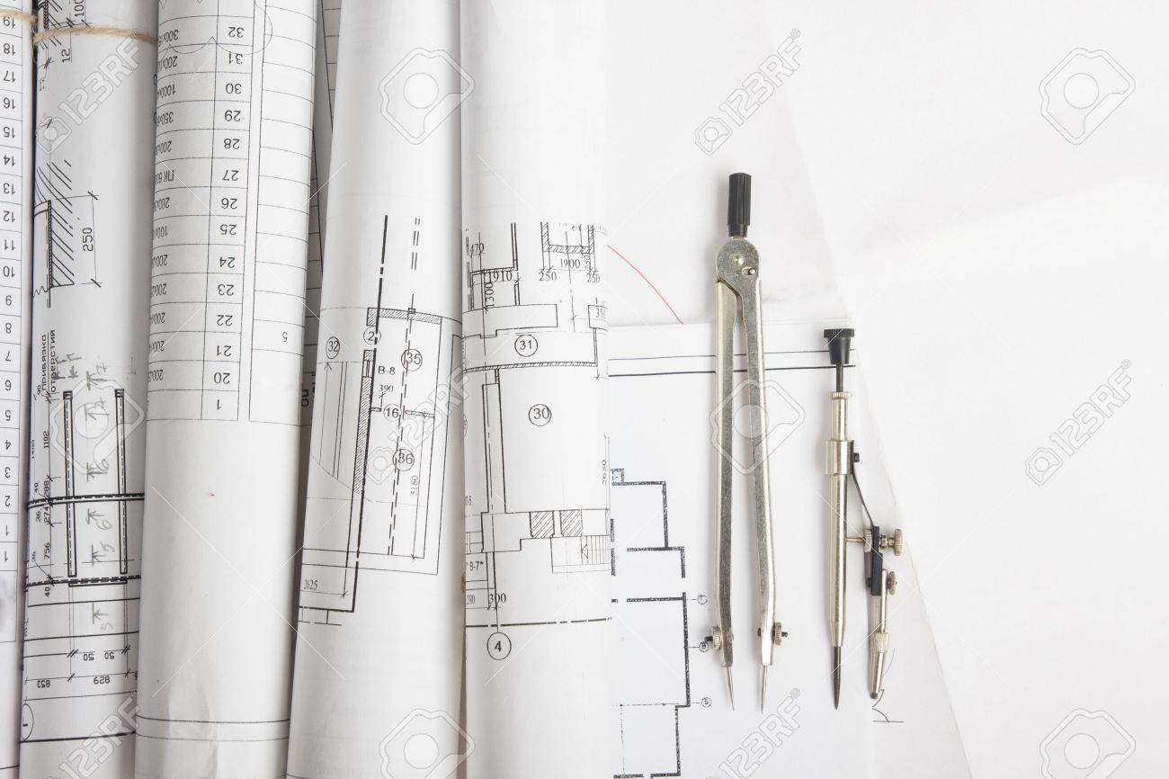 Workplace of architect - Architectural project, blueprints, rolls and tablet, pen, divider compass on plans. Engineering tools view from the top. Construction background. Copy space for text - 50996801