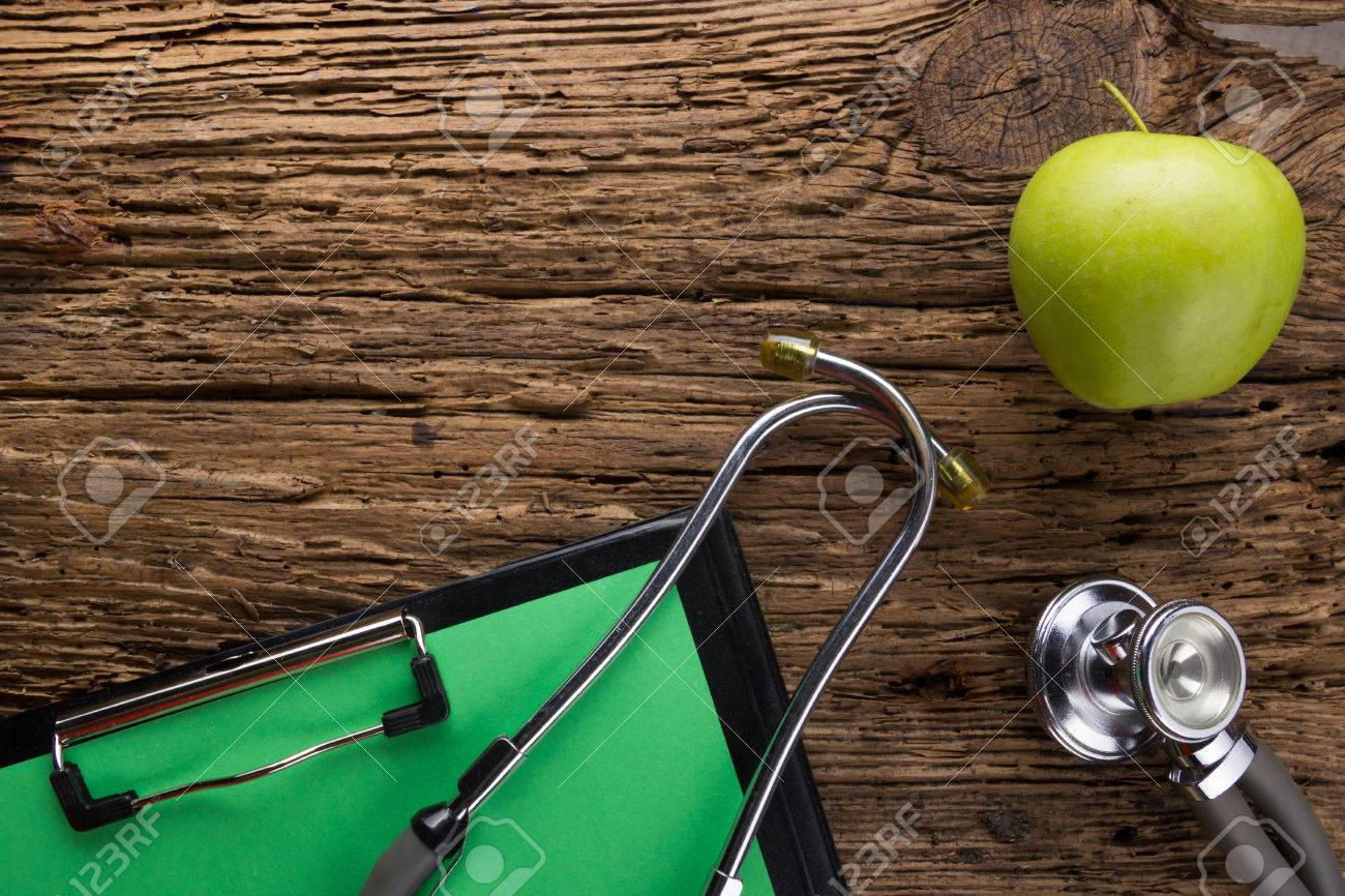 Alternative medicine - stethoscope, clipboard and green apple on wood table top view . Medical background. Concept for diet, healthcare, nutrition or medical insurance. - 50997199