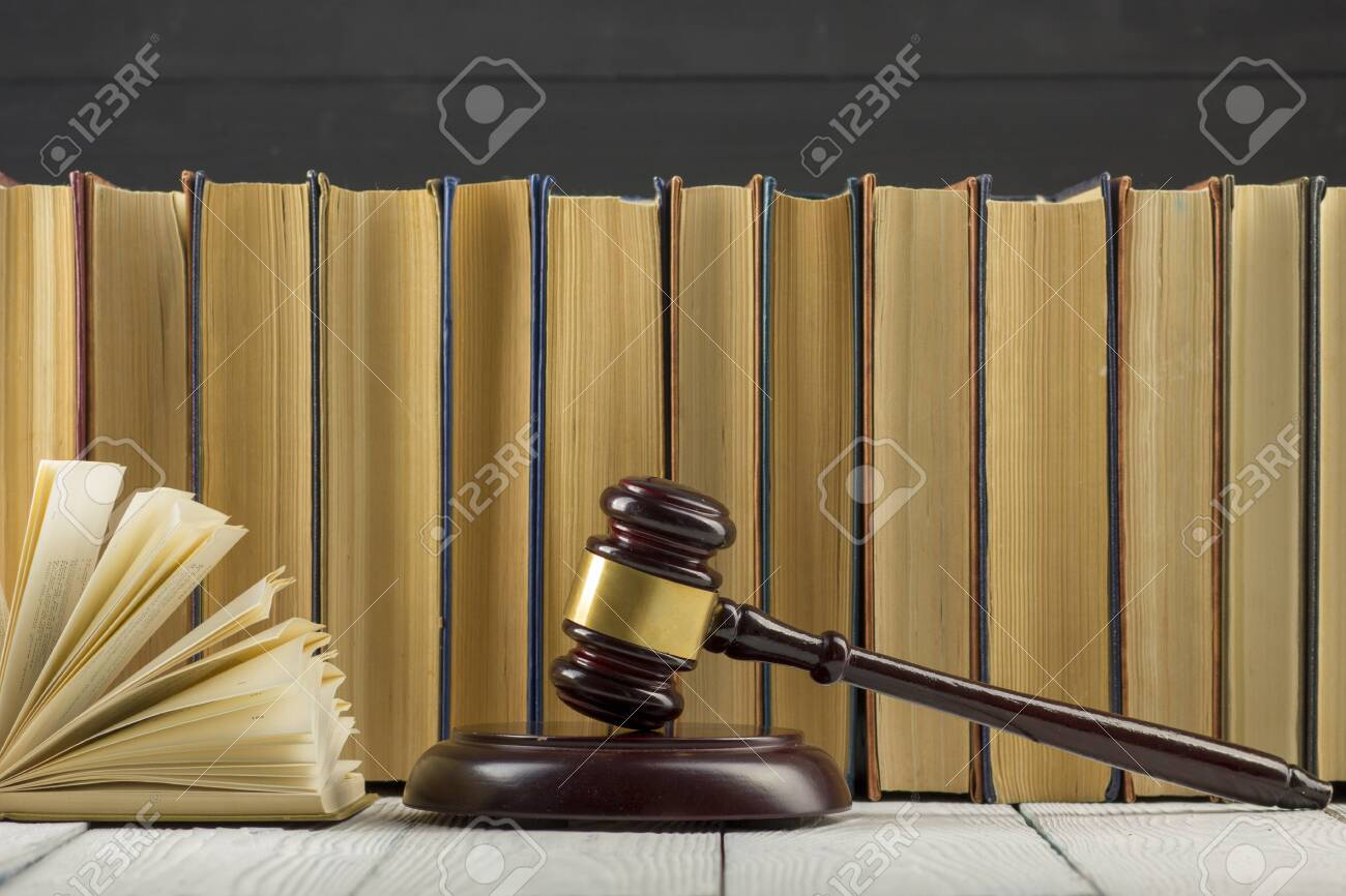 Legal Law concept - Open law book with a wooden judges gavel on table in a courtroom or law enforcement office. - 130107478