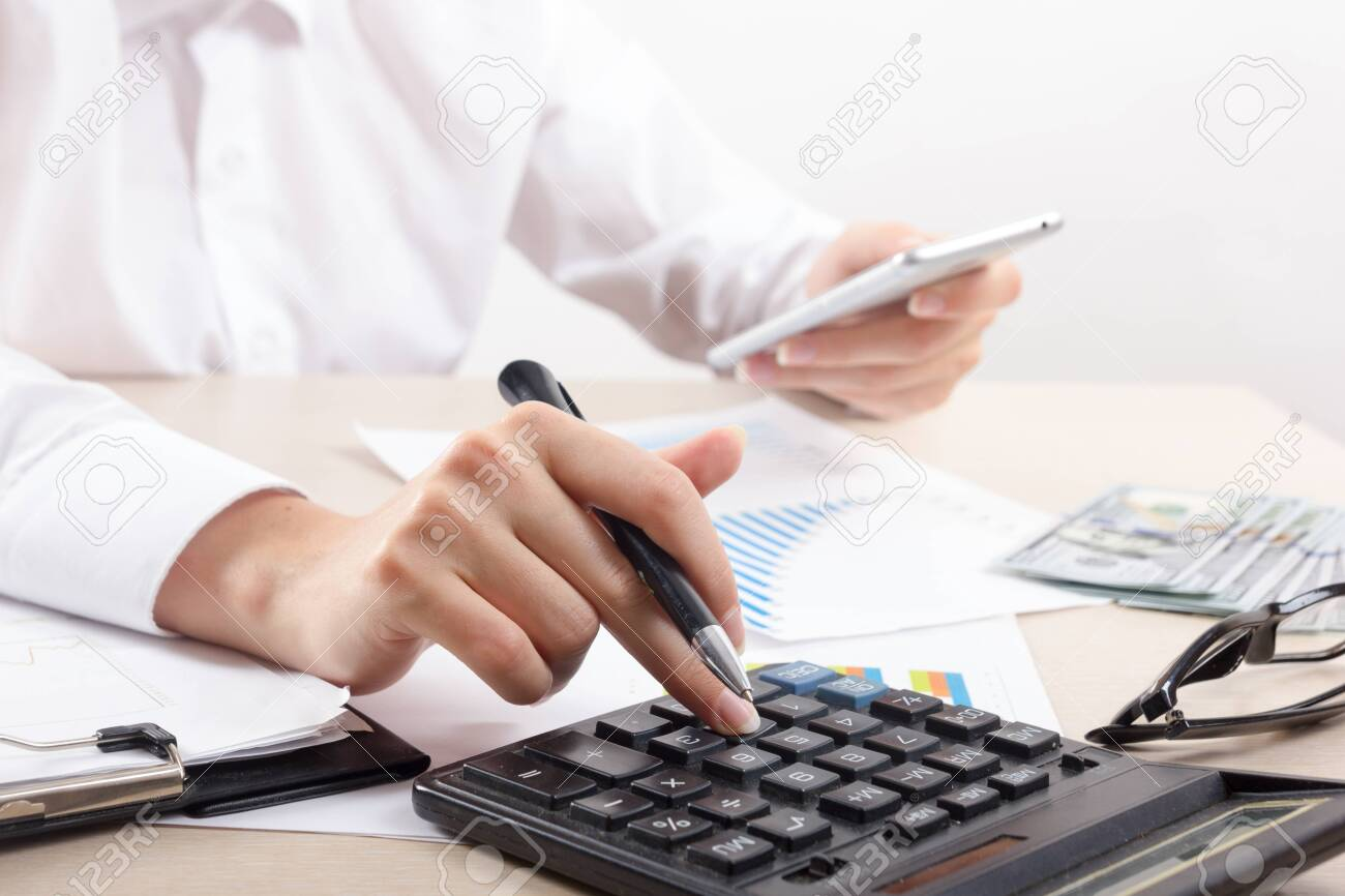 Close up of female accountant or banker making calculations. Savings, finances and economy concept - 130463078