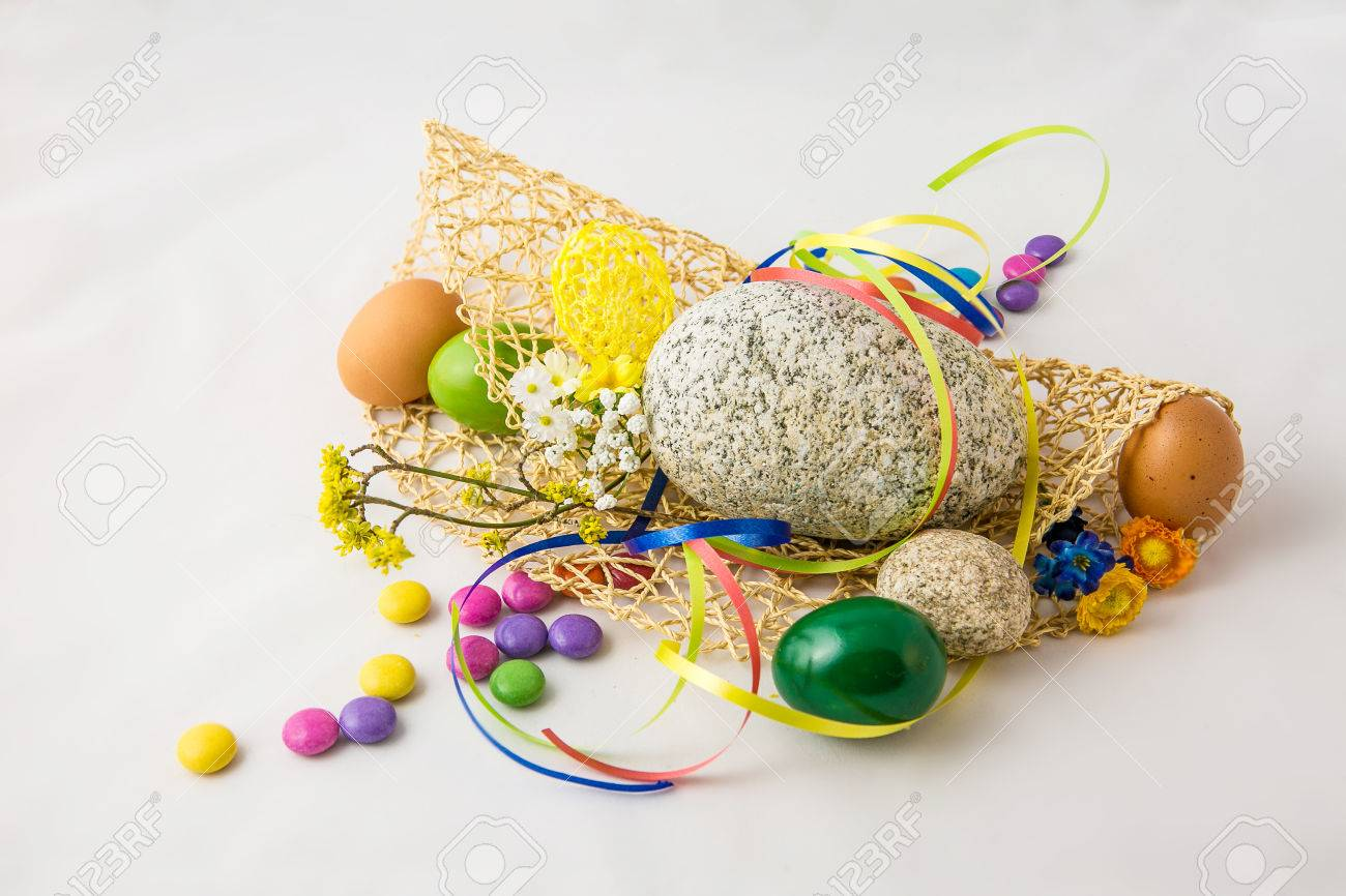 Stone and colored eggs on the white background - 58442485