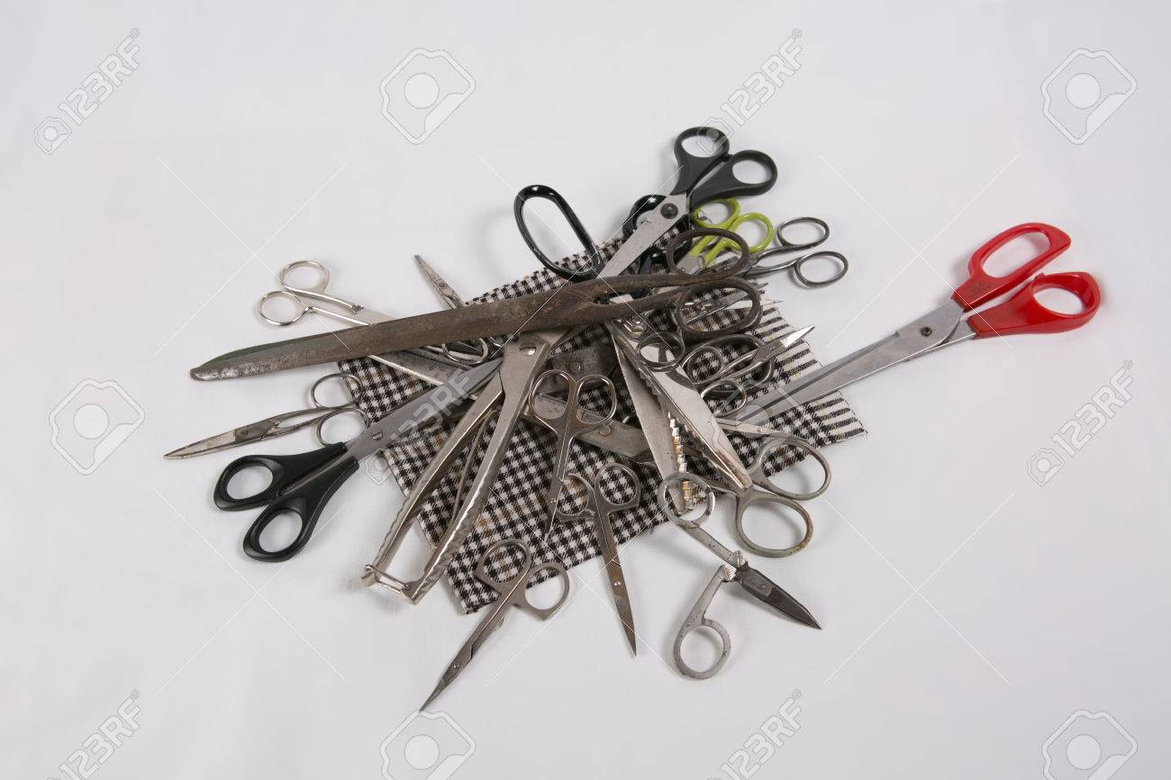 Various kinds of scissors lying on a plaid fabric - 58449336