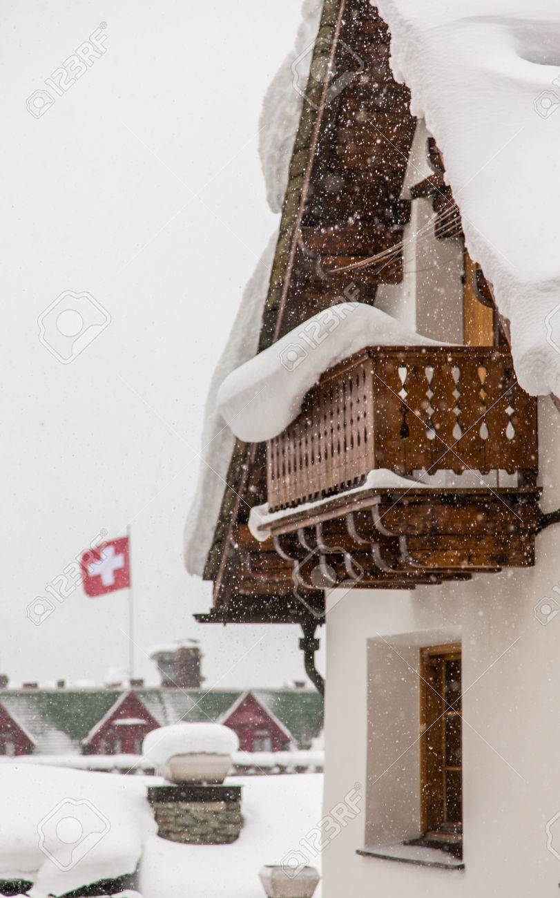 Swiss Chalet During Heavy Snow With Flag In Background Stock