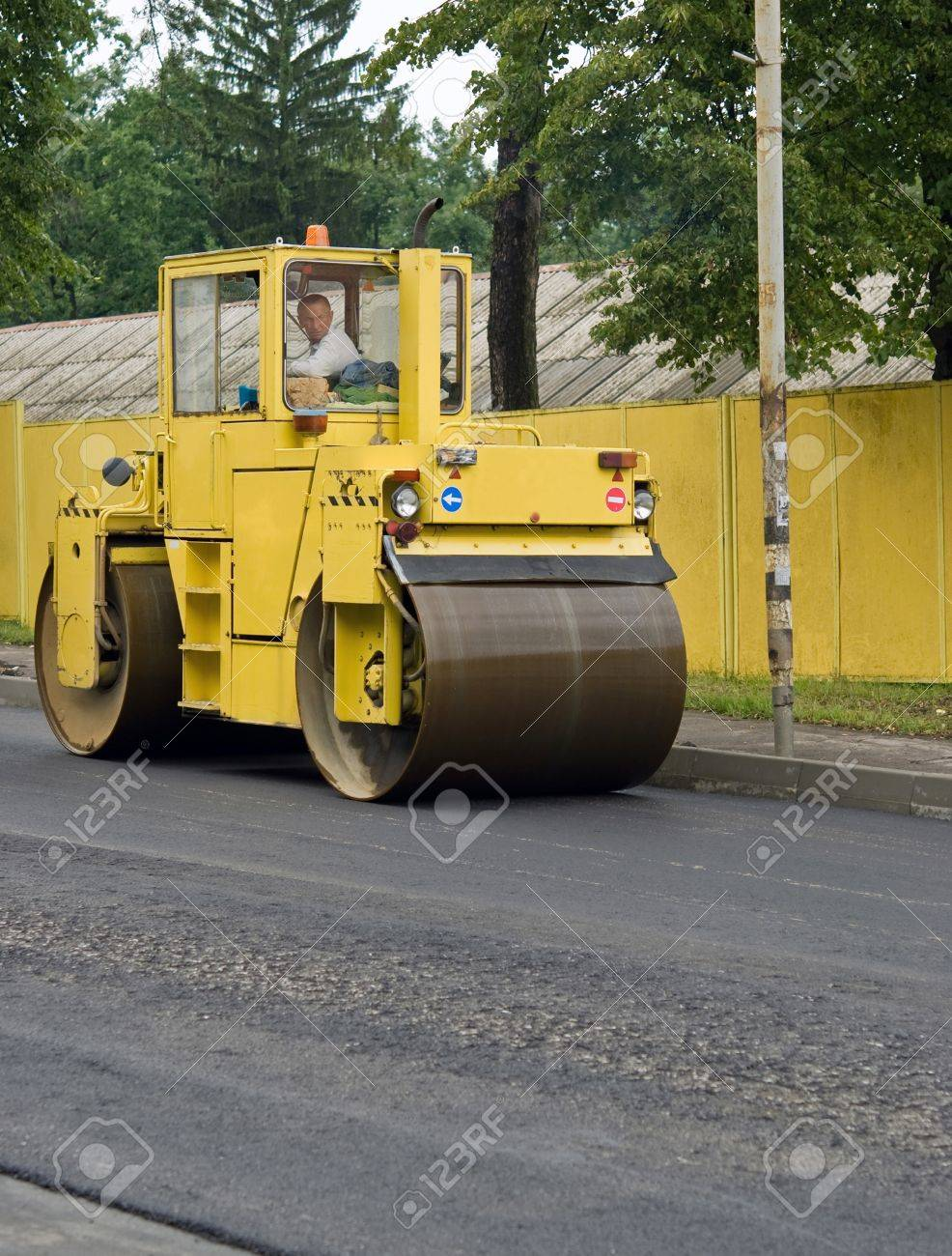 asphalt spreader is used to place the first layer of asphalt on a city street renewal project - 11298945