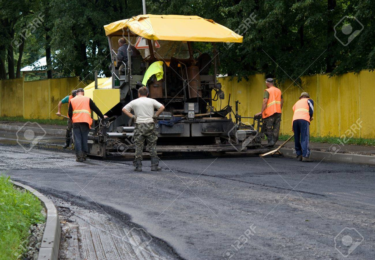 asphalt spreader is used to place the first layer of asphalt on a city street renewal project - 11297590