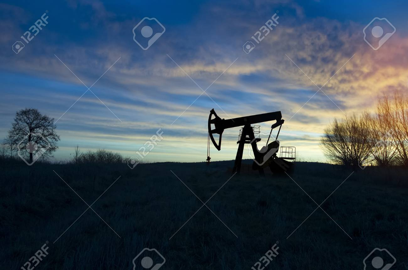 operating oil and gas well profiled on sunset sky - 108258789