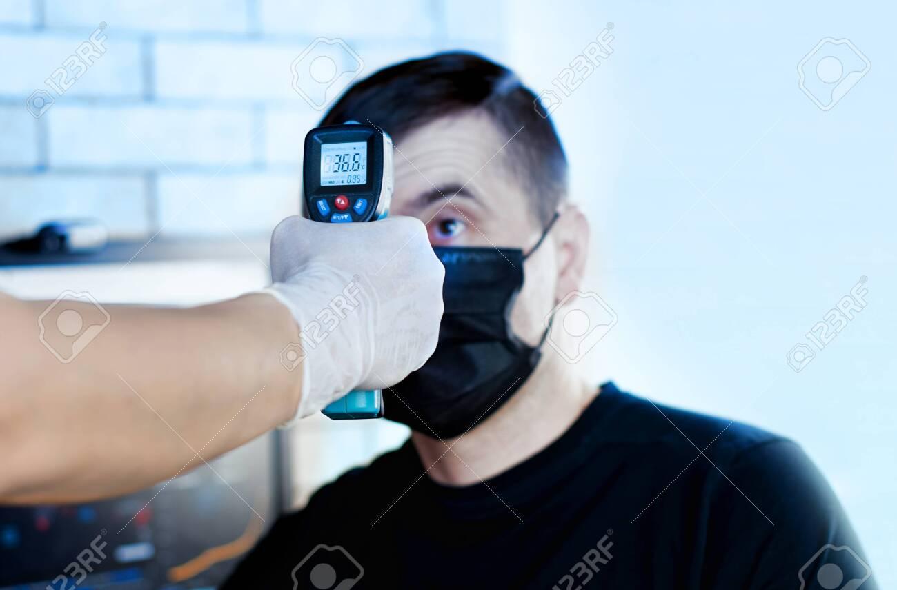 doctor measures the temperature of a man for coronavirus symptoms. - 144938000