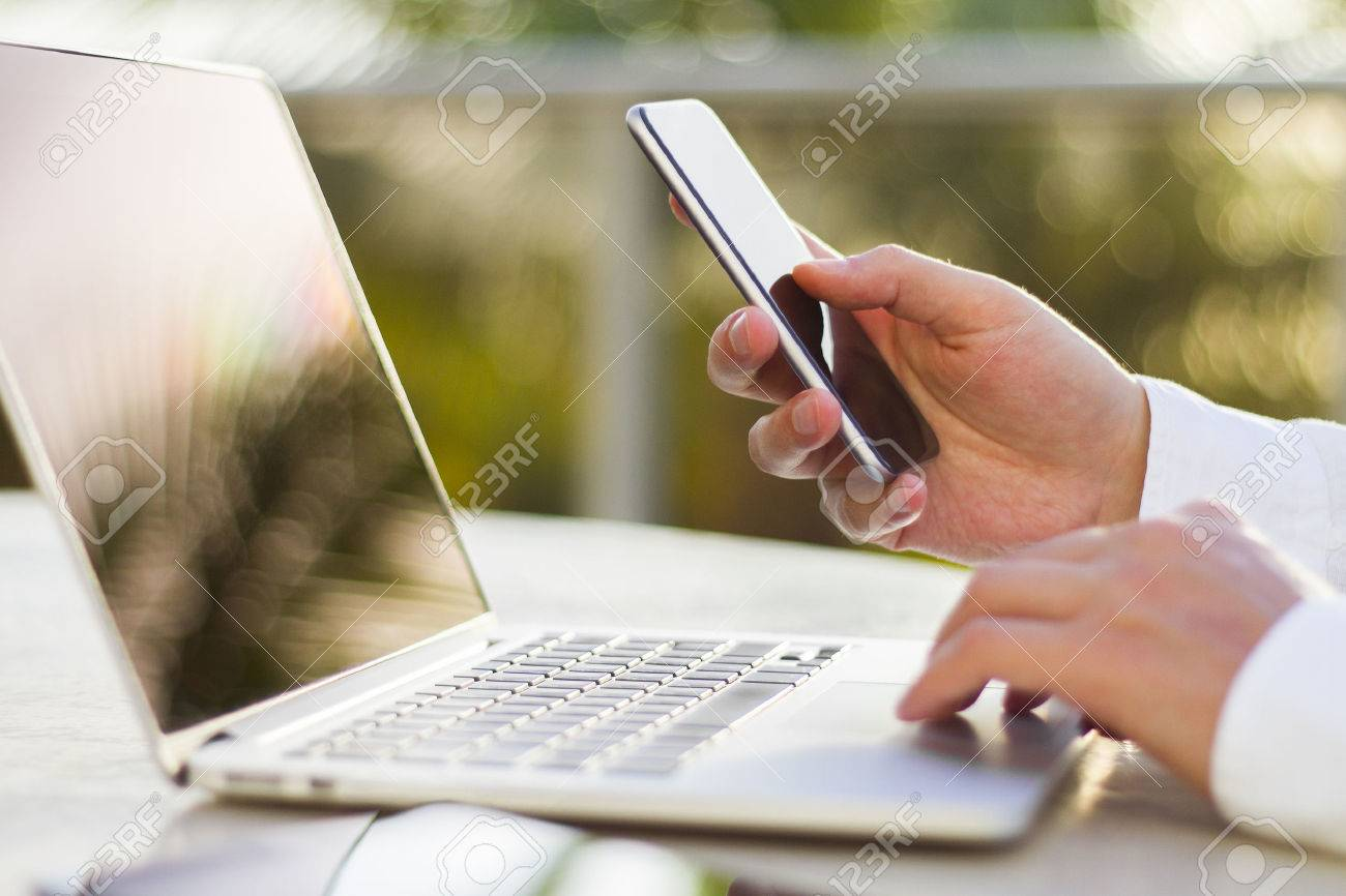businessman with cellphone and laptop at morning - 43491351