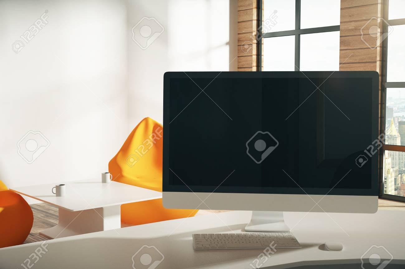 Blank écran dordinateur noir dans le bureau loft ensoleillé banque
