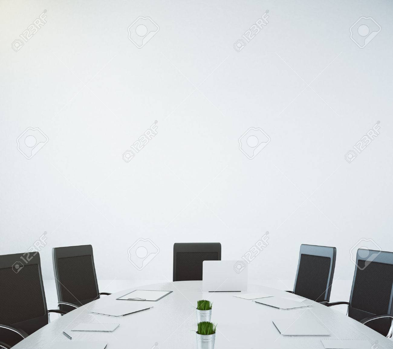 Big white oval table with laptop and chairs at white wall background - 52285612
