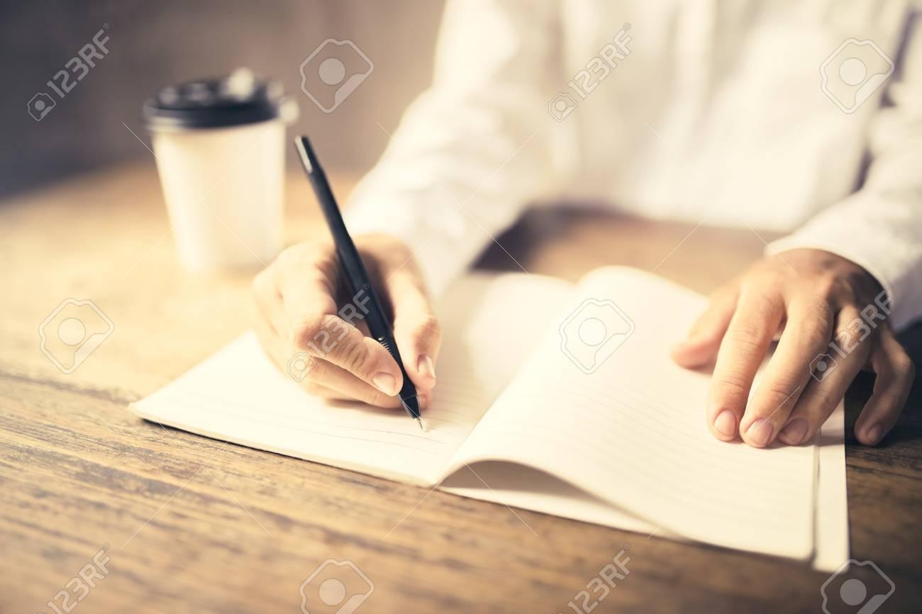 Fille écrit dans le bloc notes sur un bureau en bois avec une tasse