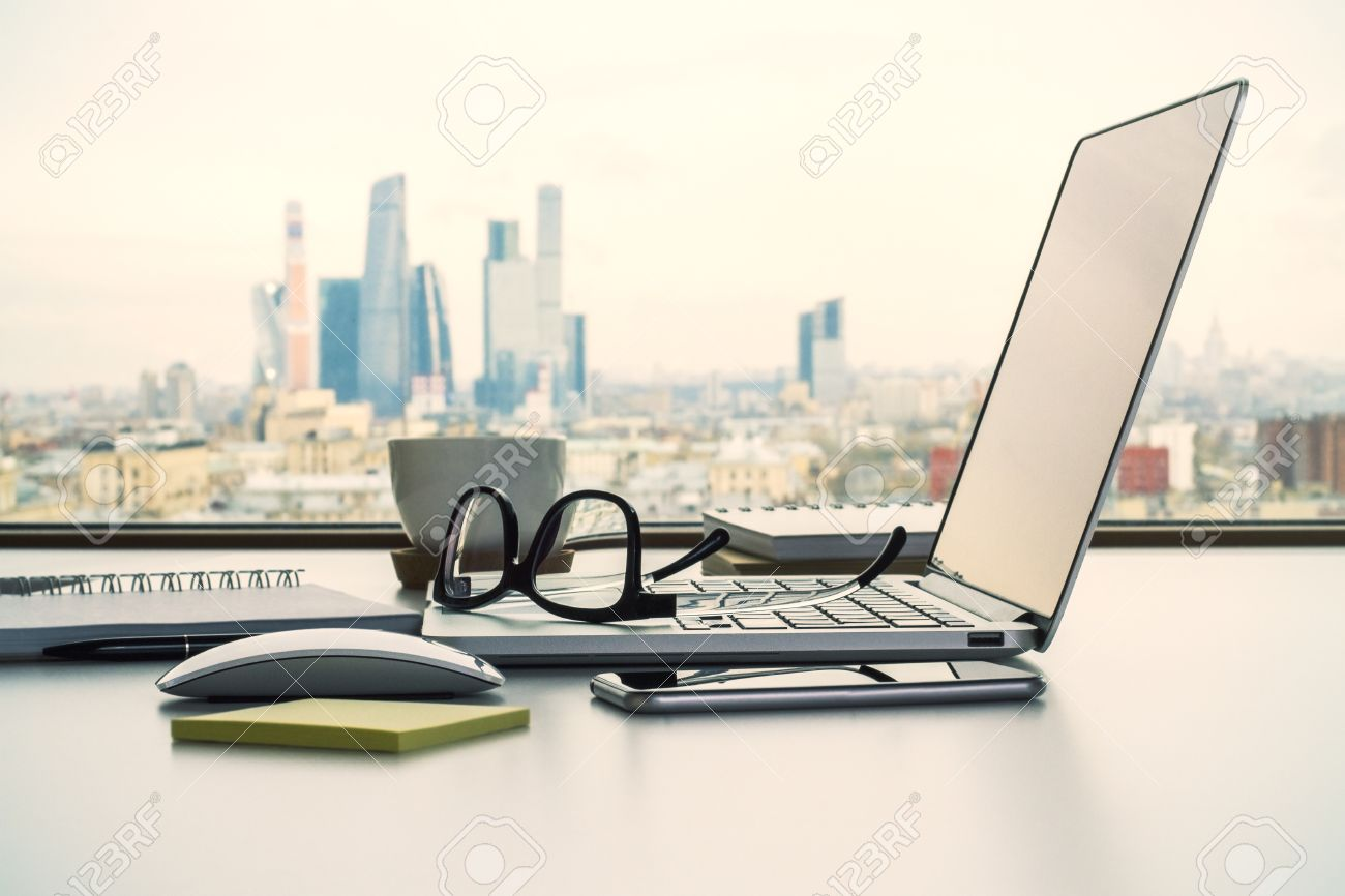 laptop office desk. Sideview Of Office Desk With Laptop, Glasses And Other Items On Moscow City Background Stock Laptop ,
