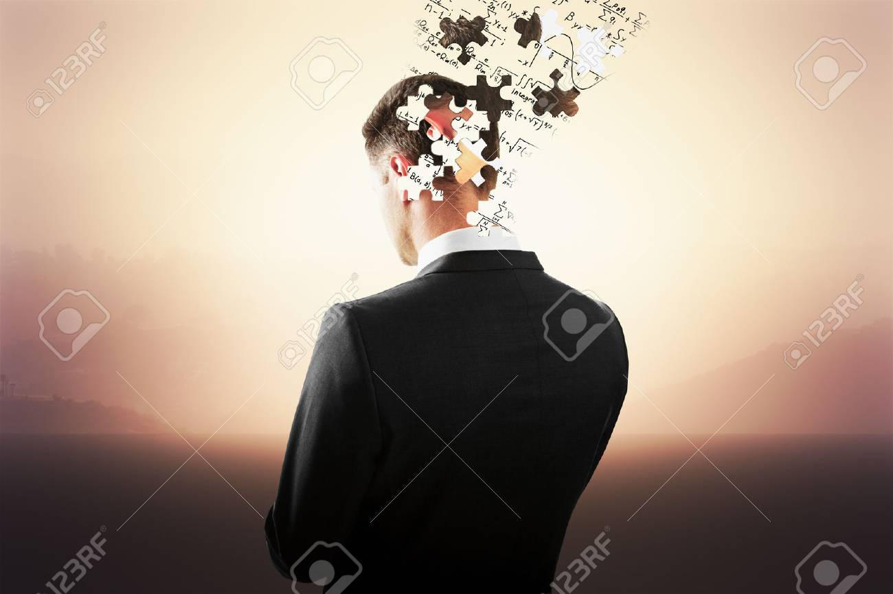 888f89dc4d7f Businessman head breaking into puzzle pieces on misty landscape background.  Brainstorming concept Stock Photo -