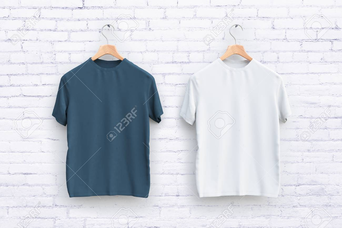 Hangers with empty grey and white t-shirts hanging on brick wall
