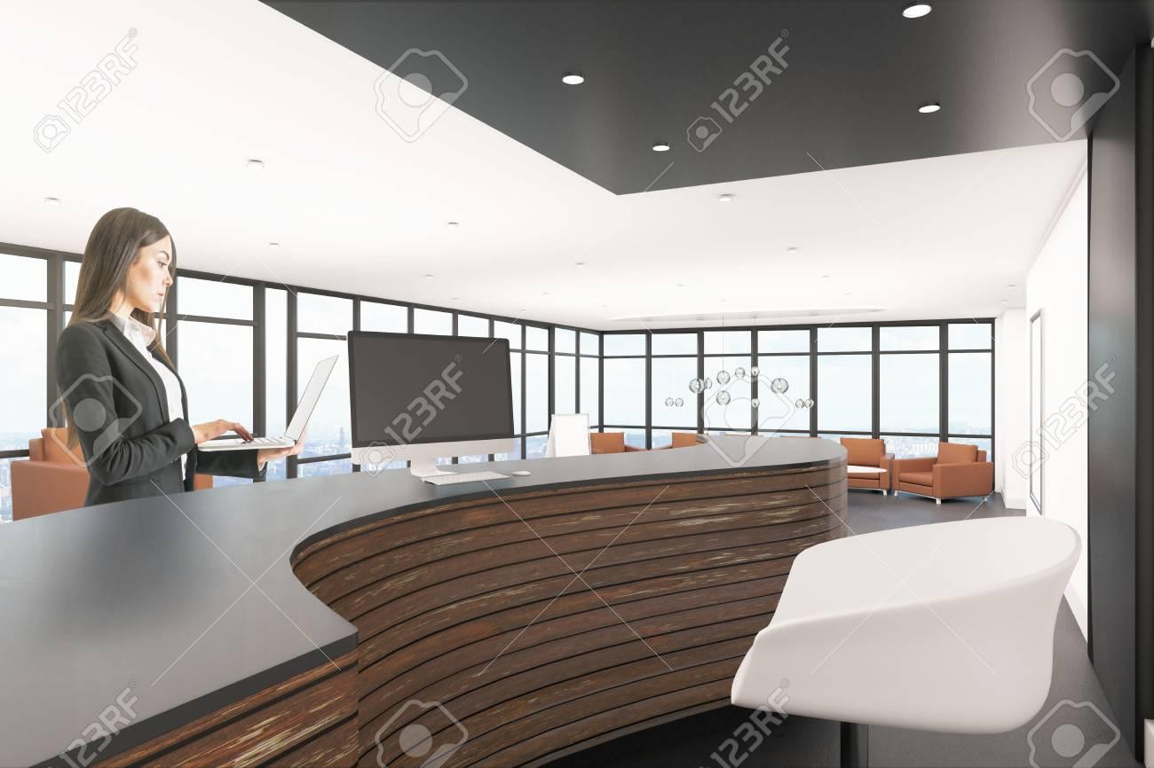 Attractive businesswoman standing in modern office lobby interior..
