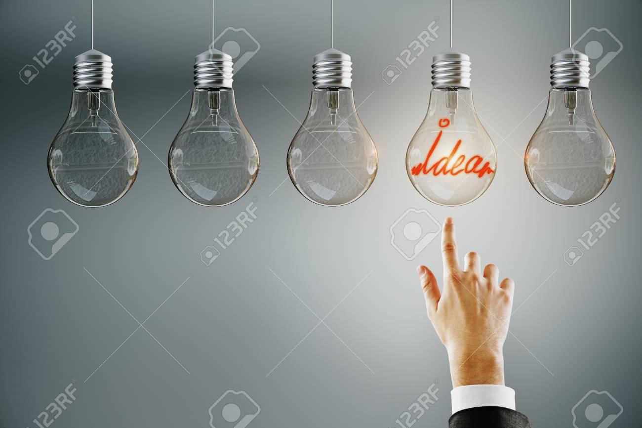 Hand pointing at row of illuminated light bulbs on subtle background. Leadership, idea and choice concept - 123065166