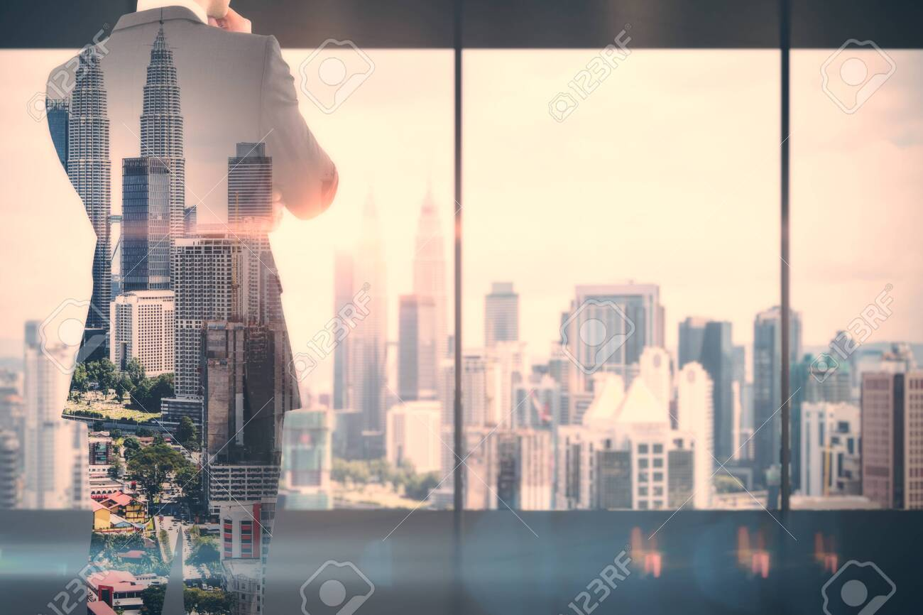 Back view of thoughtful young businessman standing in modern business interior with Kuala Lumpur city view. Success and research concept. Double exposure - 123065317