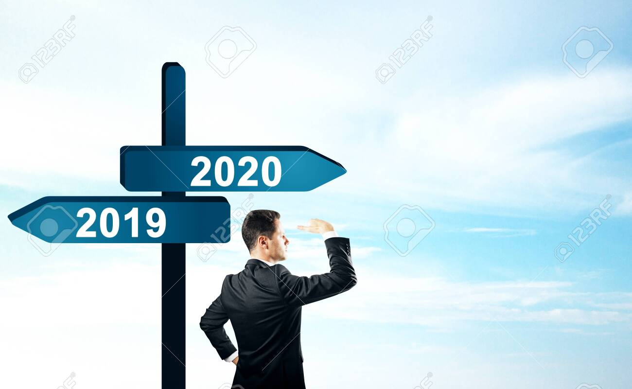 Side view of attractive businessman standing and looking into the distance on abstract year 2019, 2020 direction sign board on sky background. Happy New Year, research and future concept - 124293590