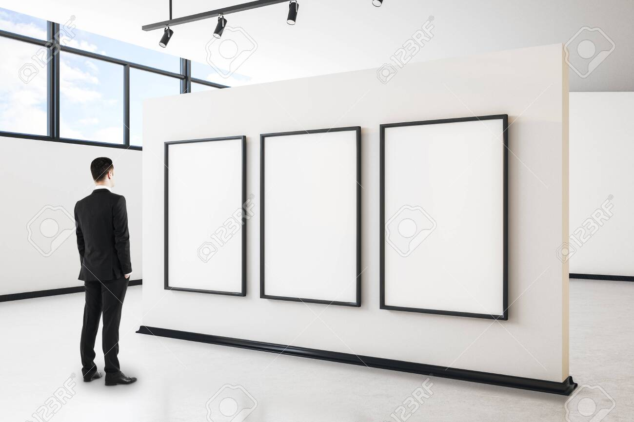 Businessman in modern gallery interior with city view, empty poster and daylight. Mock up, - 124848588