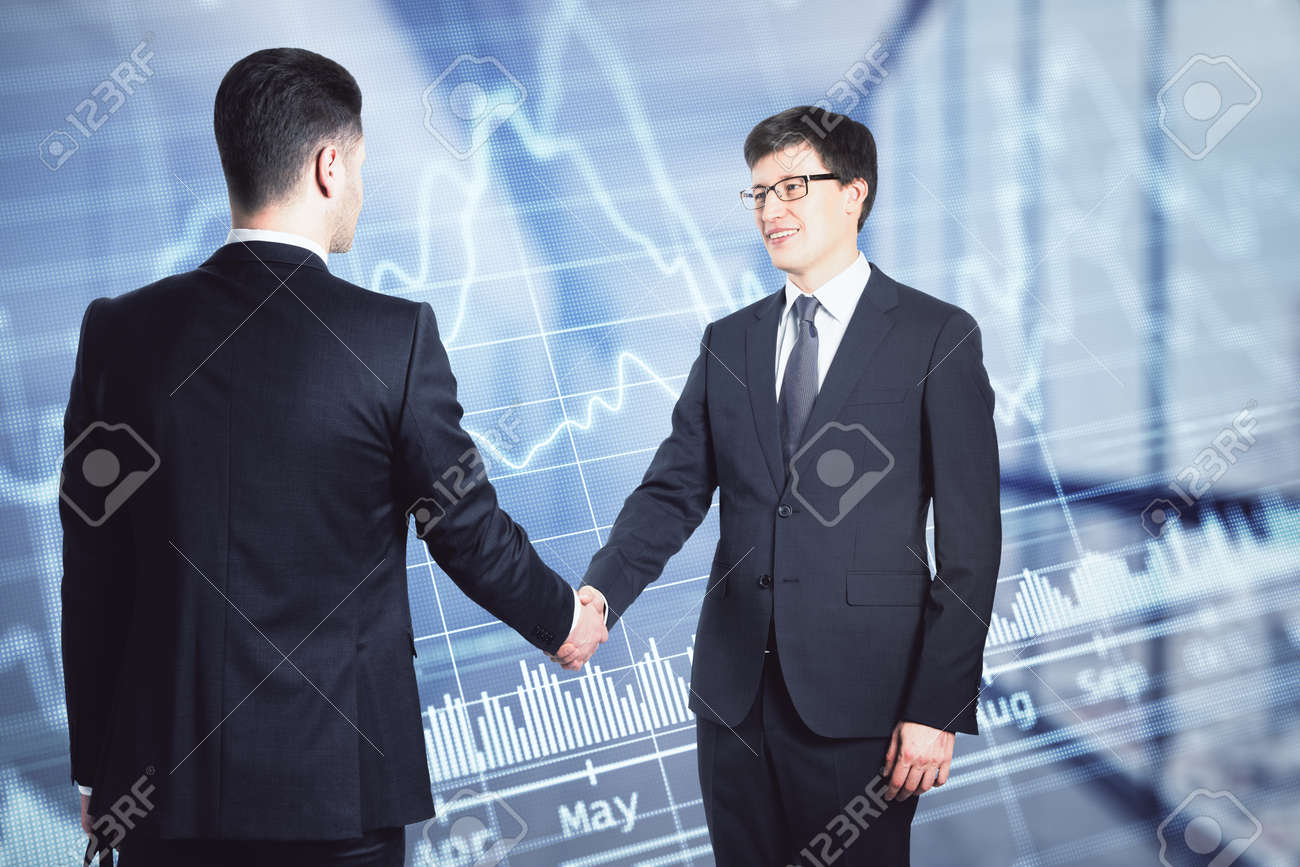 Two businessmen in suits shaking hands on the background of financial chart in office, deal and partnership concept - 159497780