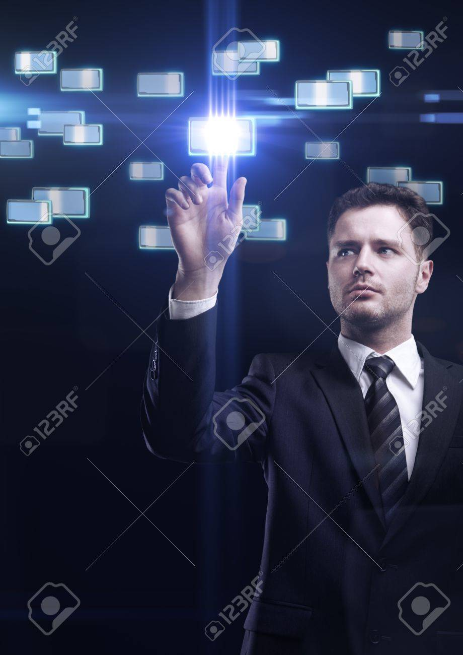 Young business man pressing a touchscreen button Stock Photo - 10400907
