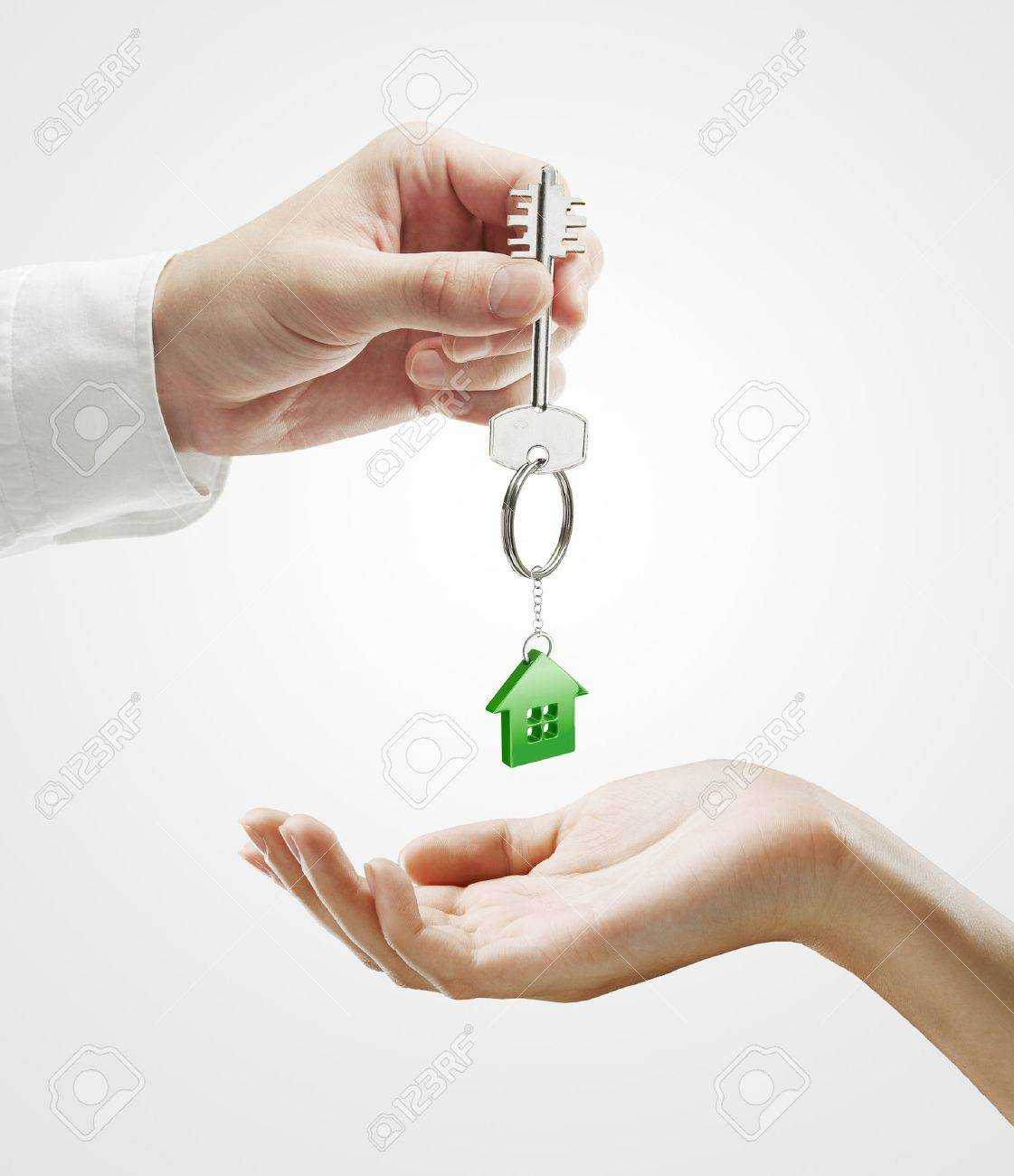 Man is handing a house key to a woman.Key with a keychain in the shape of the house. On a gray background Stock Photo - 10663324