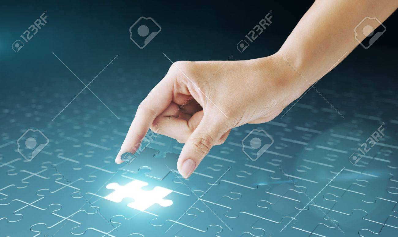 Hand embed missing puzzle piece into place. Business concept for completing the final puzzle place Stock Photo - 10663326