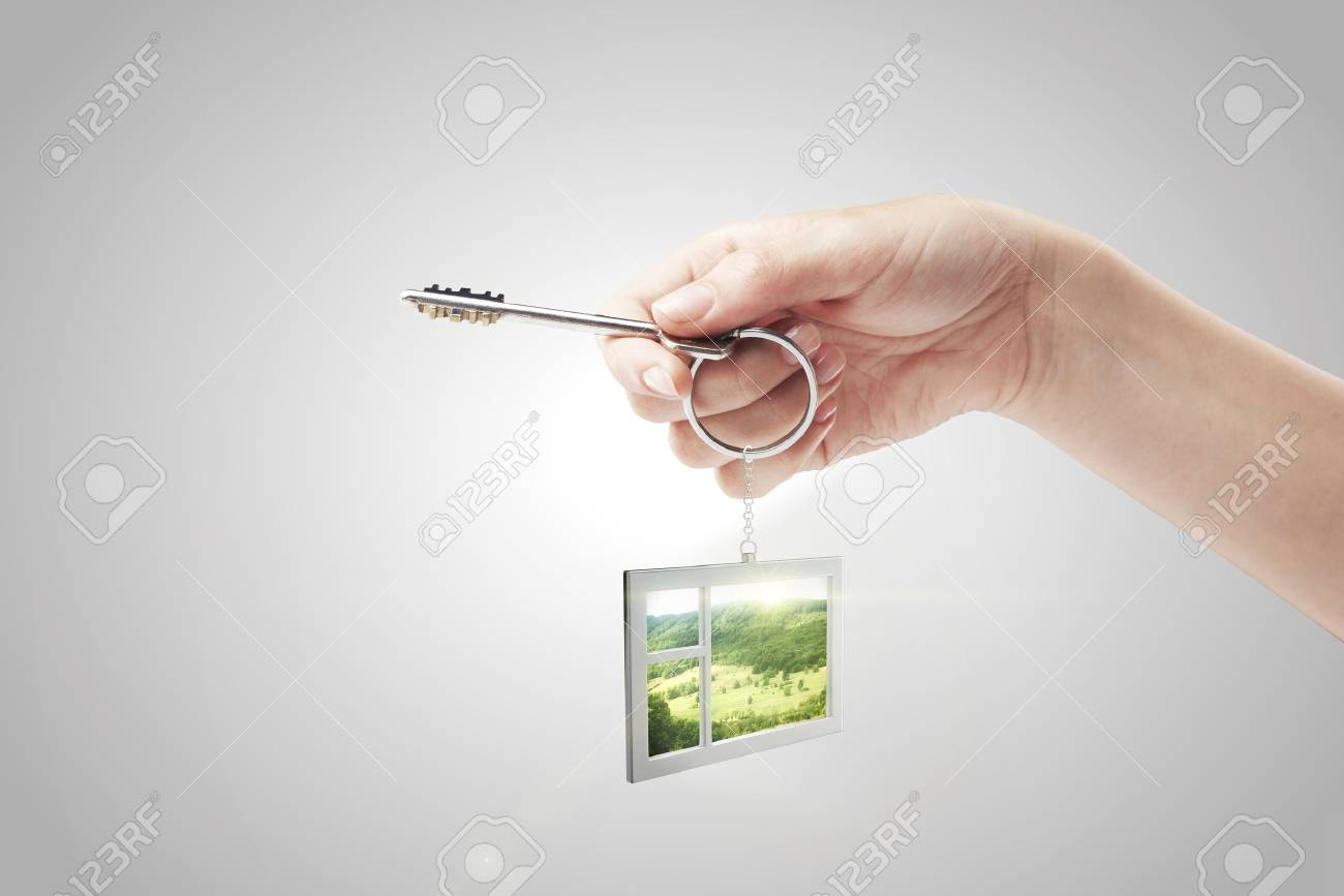 Hand holding key with a keychain in the shape of the window. Beautiful view behind a window of a green field with a blue sky. House key on a gray background Stock Photo - 11031243