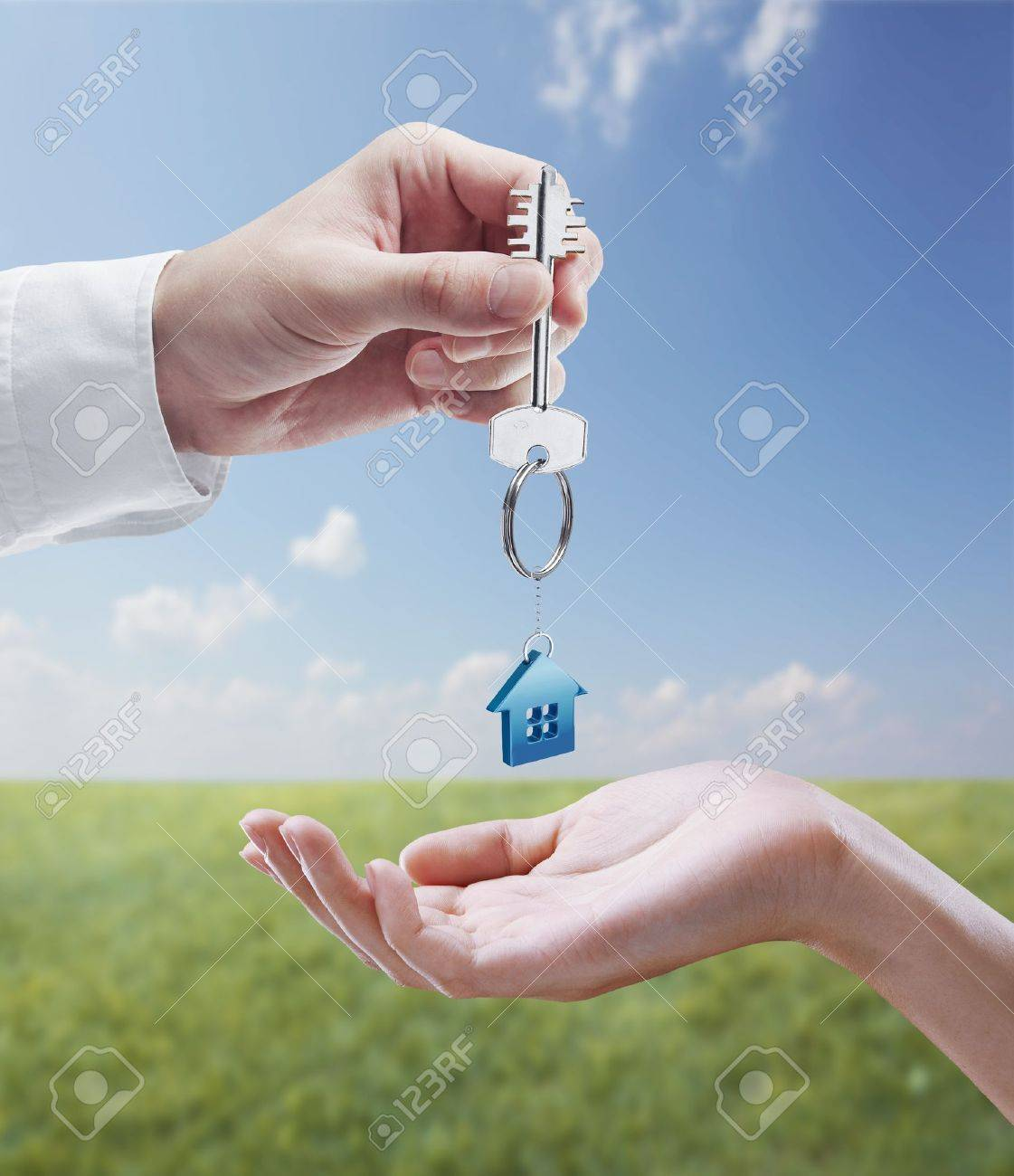 Man is handing a house key to a woman.Key with a keychain in the shape of the house. On background of nature Stock Photo - 11286414