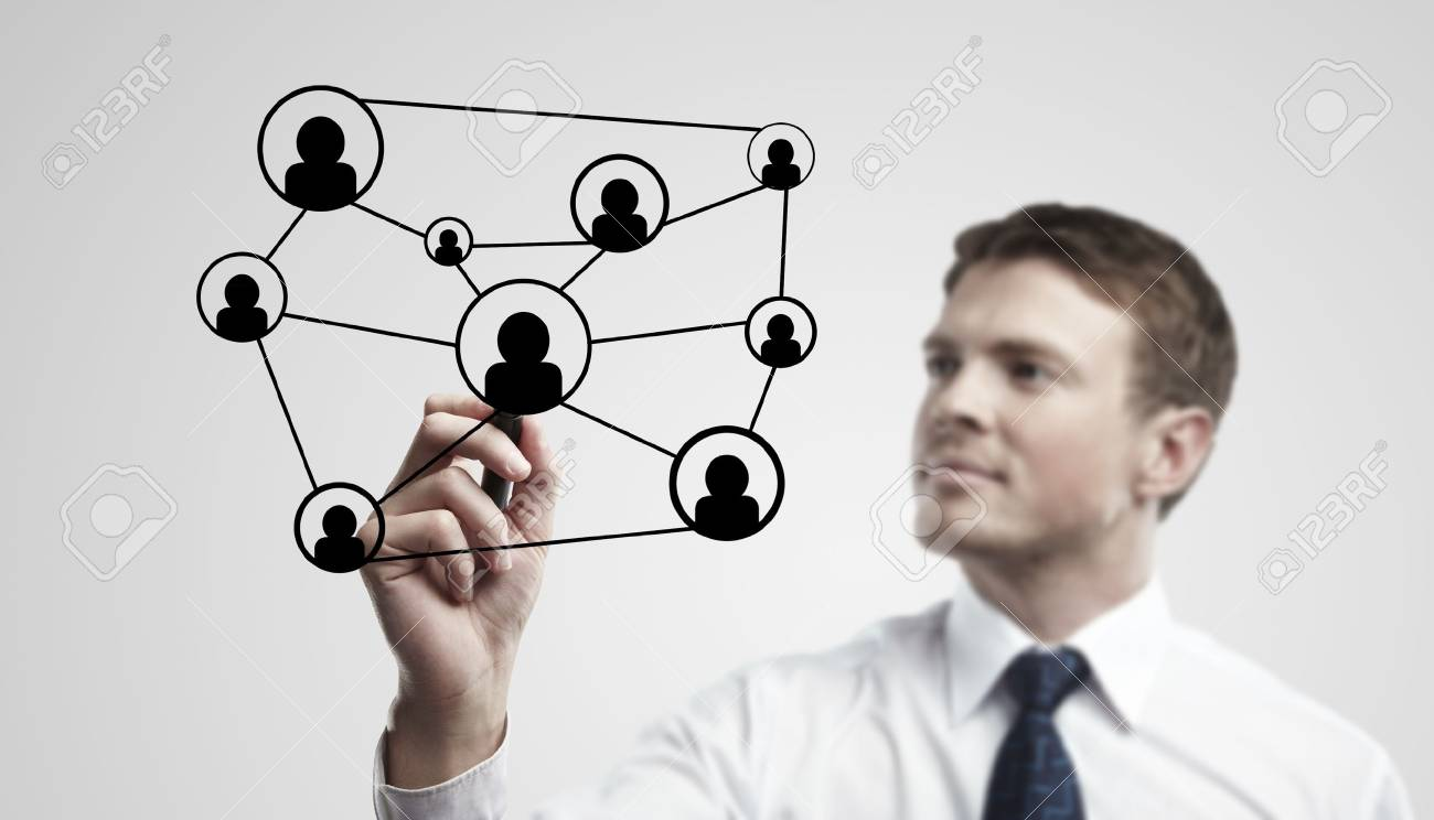 Young business man drawing a social network or globalization concept.  Man drawing a global network on a glass window. On a gray background. Stock Photo - 11788905