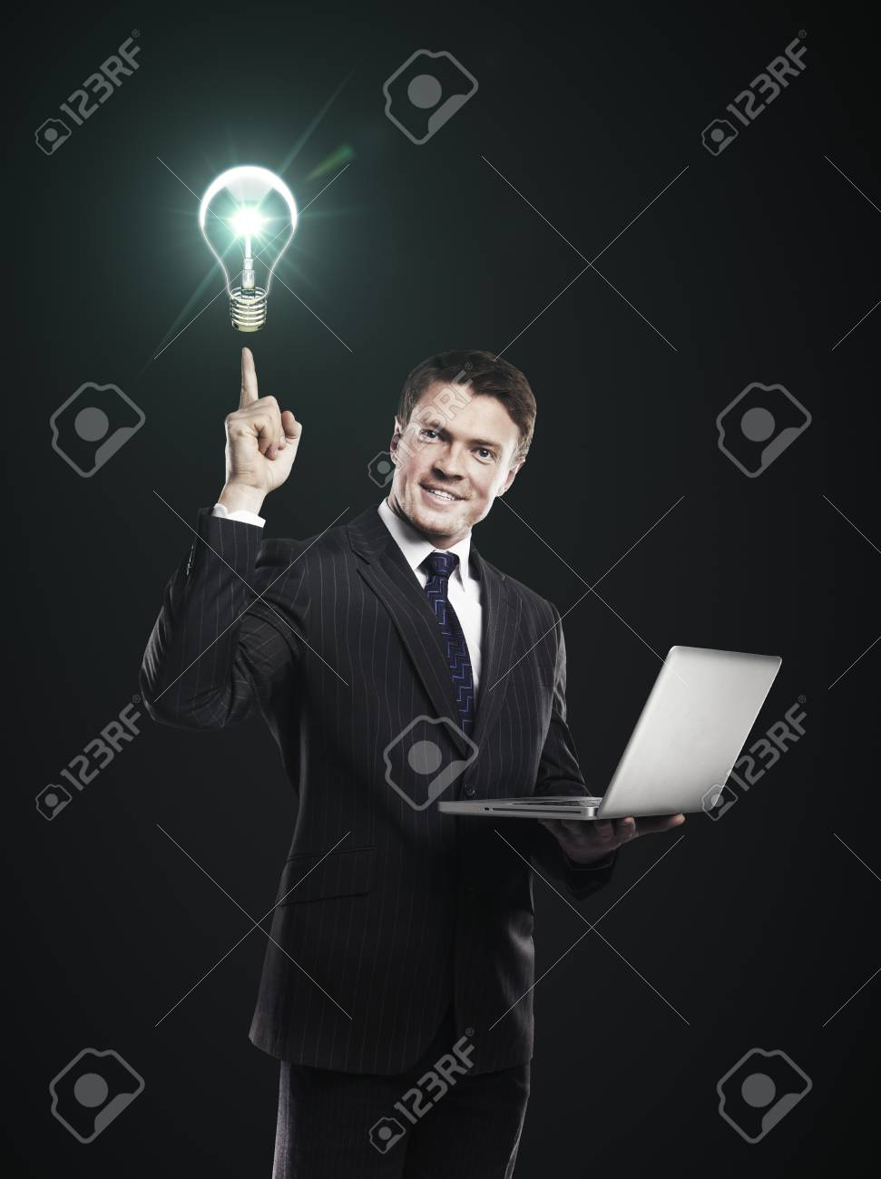 businessman with laptop in hand points to the light bulb Stock Photo - 14165910
