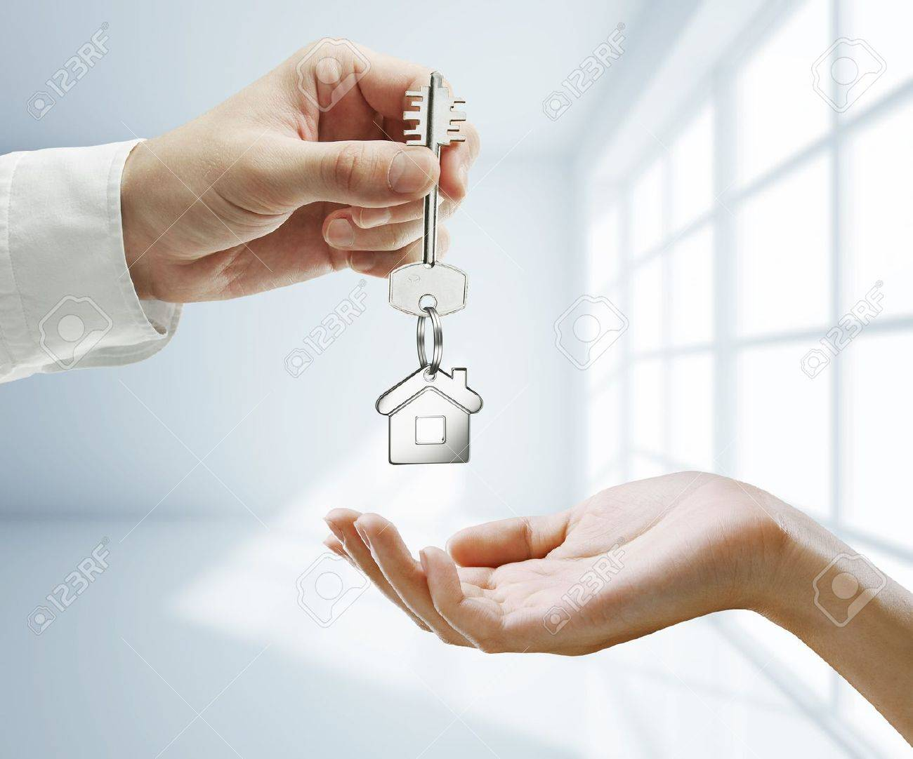 passing key against backdrop of white room Stock Photo - 15061688