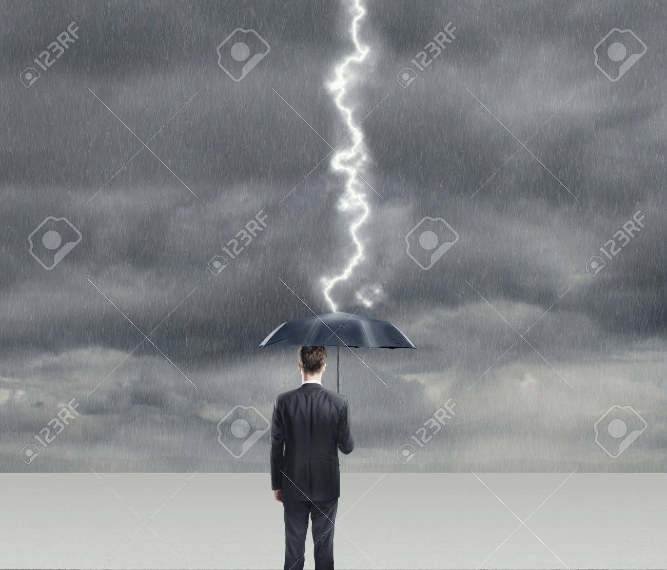 Businessman with umbrella in thunderstorm Stock Photo - 18039727